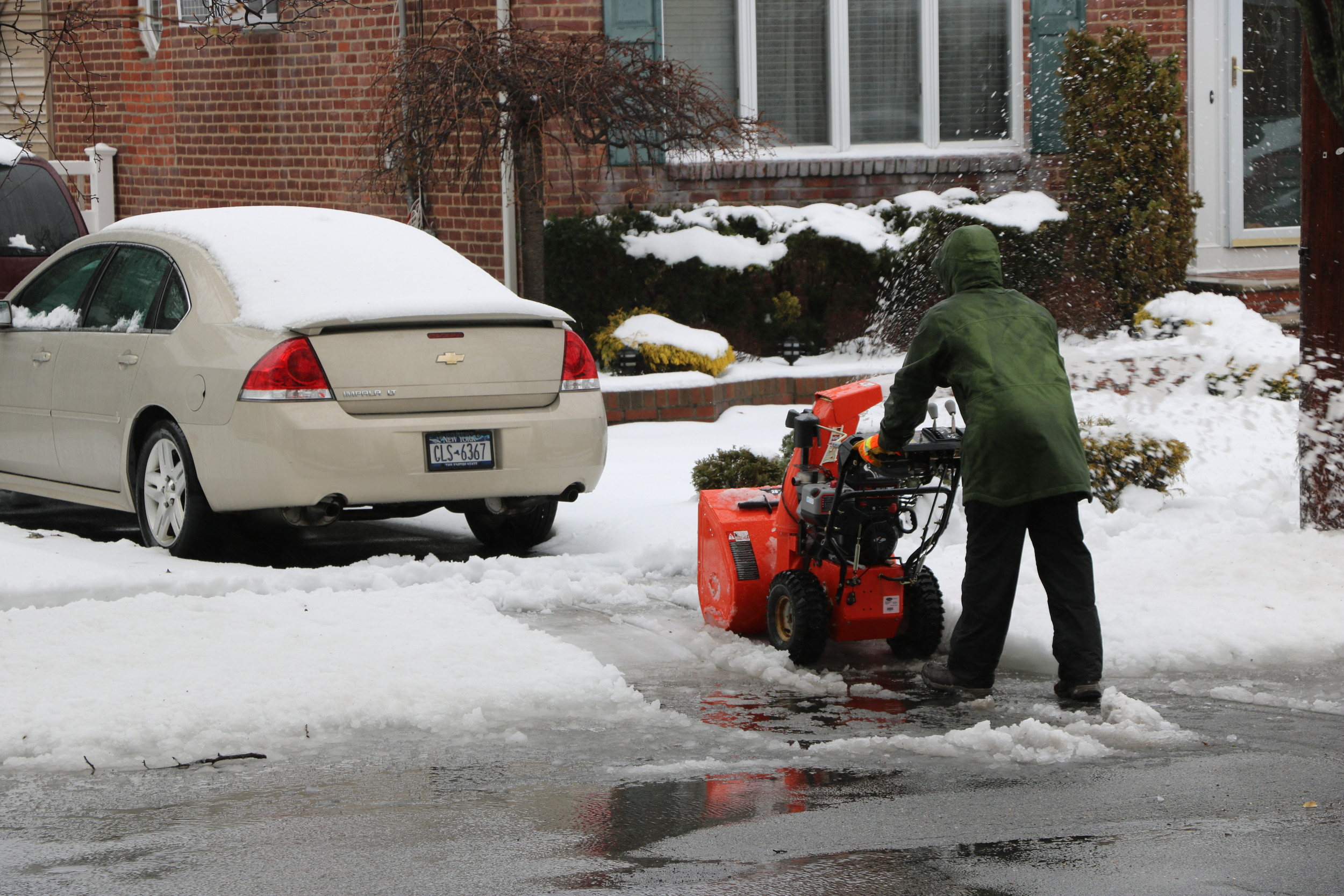 A Malverne resident blew away wet, heavy snow while standing in puddles of freezing rain.