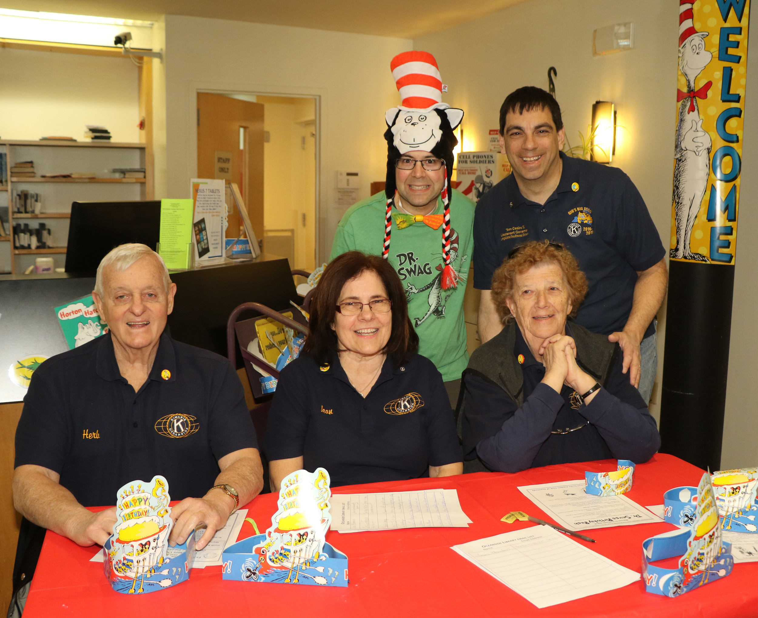 Michael Ambrosio, wearing green, along with Oceanside Kiwanis Lt. Gov. Thomas Cesiro, Herb Faust, Jean Kramer and Joan Ivarson welcomed visitors at Oceanside Library's Dr. Seuss Birthday Bash on March 5.