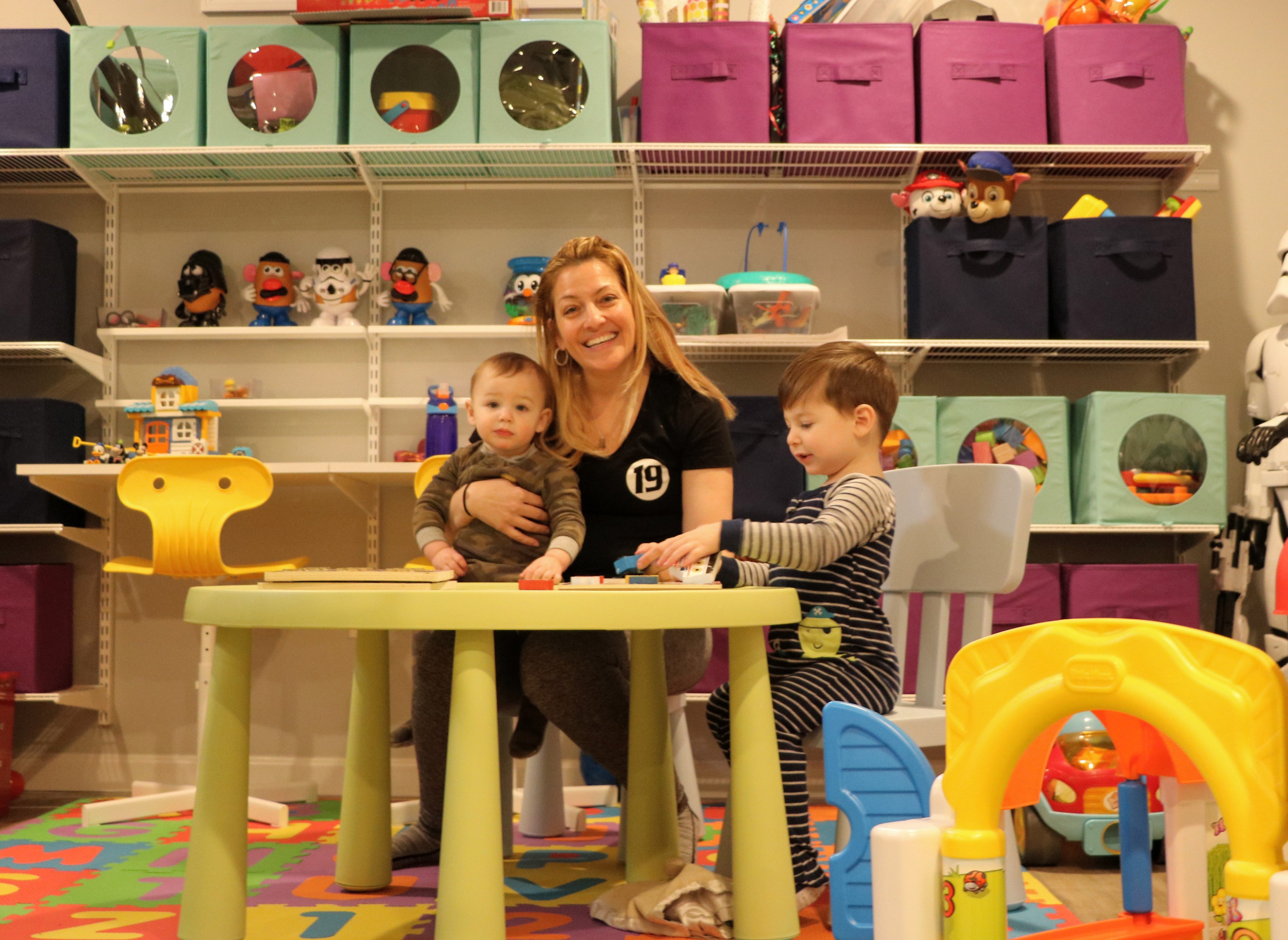 "Kelly and her children in her home's basement, with toy shelves, table, chairs, and more supplied courtesy of the ""Harry"" show."