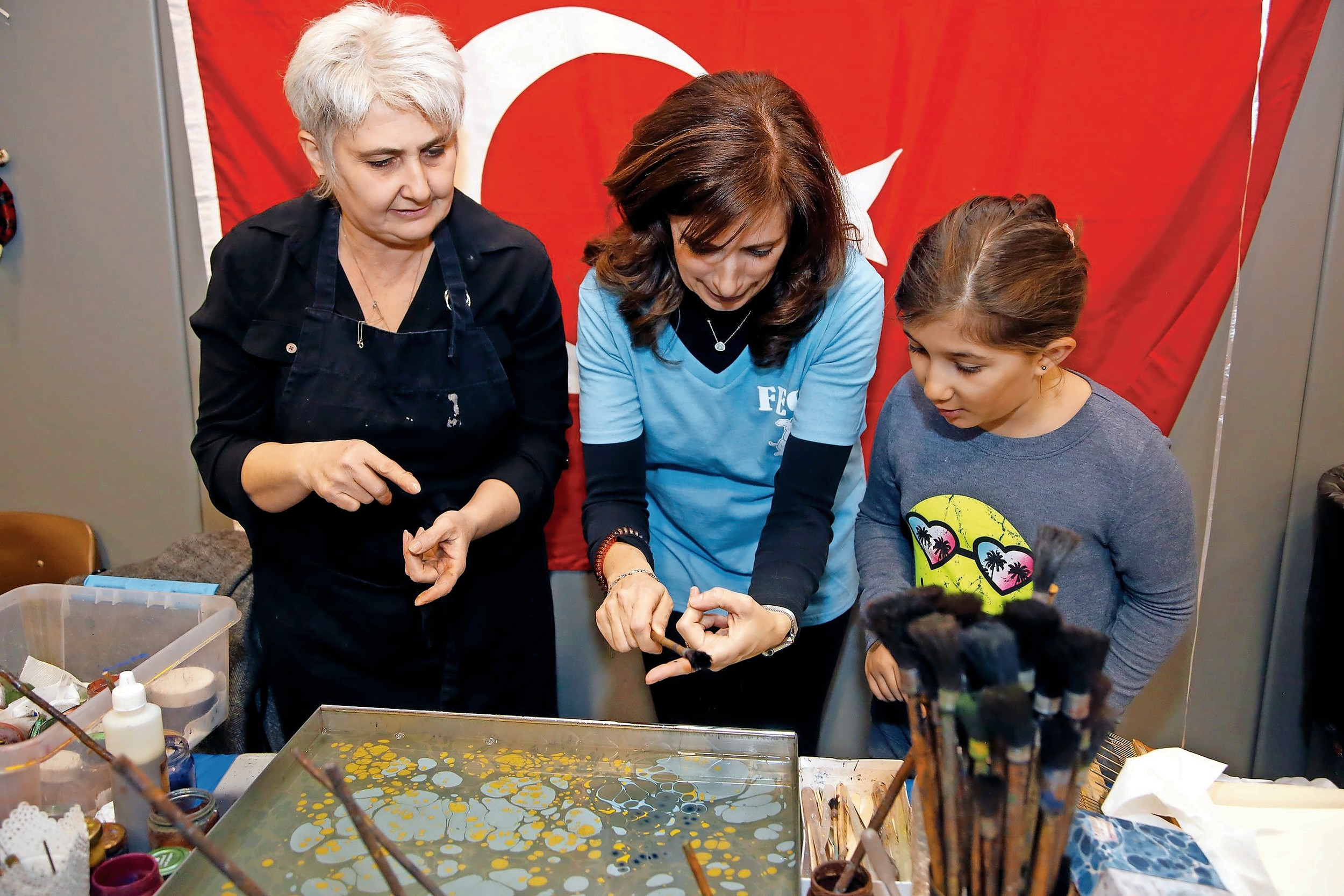 Turkish artist Bingul Sevimli oversaw Franklin Early Childhood Center Principal Lorraine Smyth, center, and Deniz Artan create a piece of artwork.