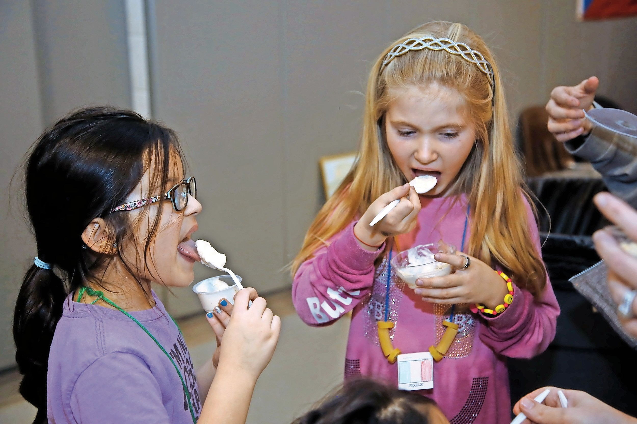 Ava Gupta and Ava Spinner, both 6, tasted their Italian panna cotta at the One World Celebration.