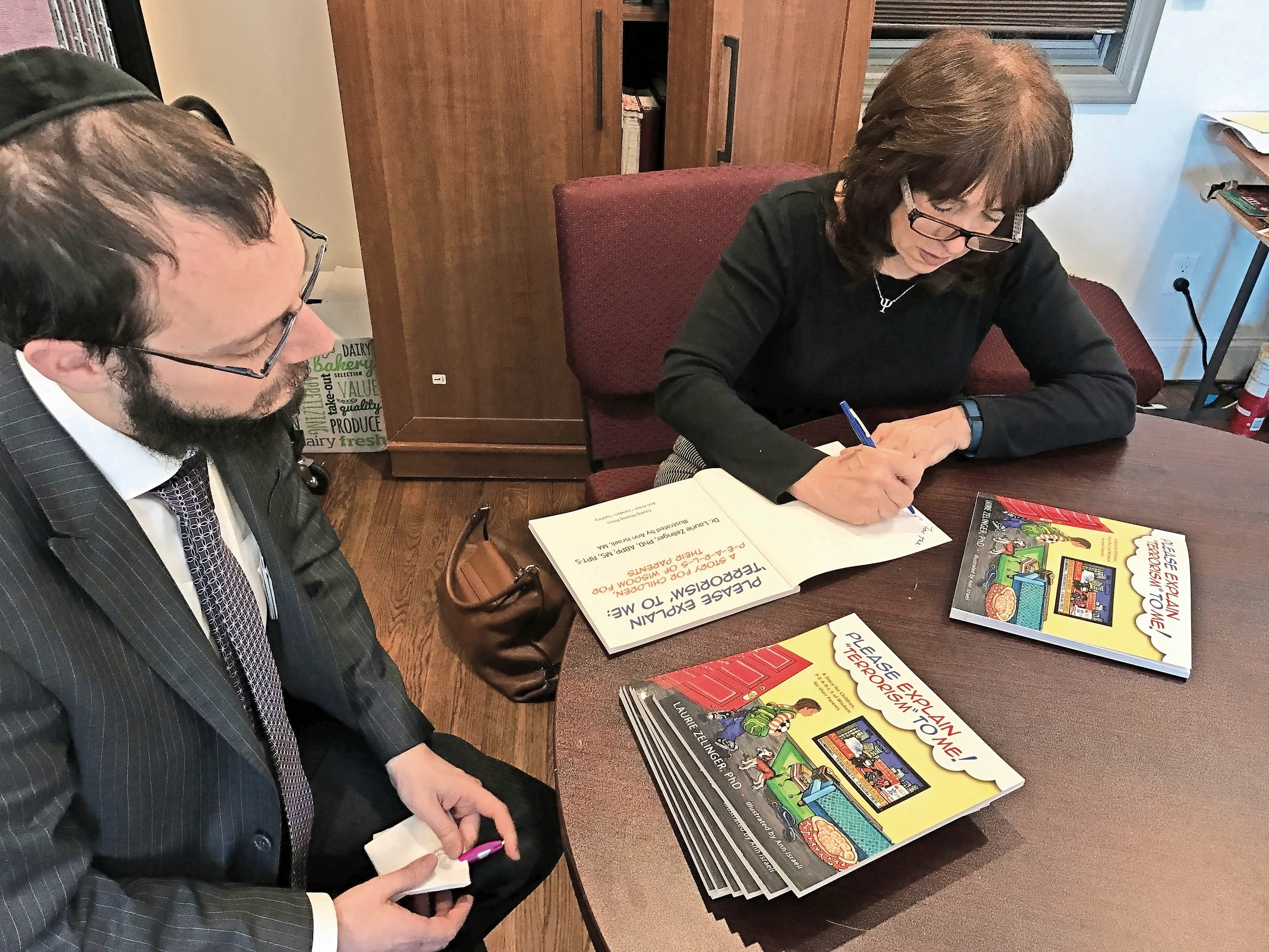 Dr. Laurie Zelinger, an author and child psychologist from Cedarhurst, signed the copies of her books that will be delivered to Israel this week. At left was Rabbi Nochem Tenenboim.