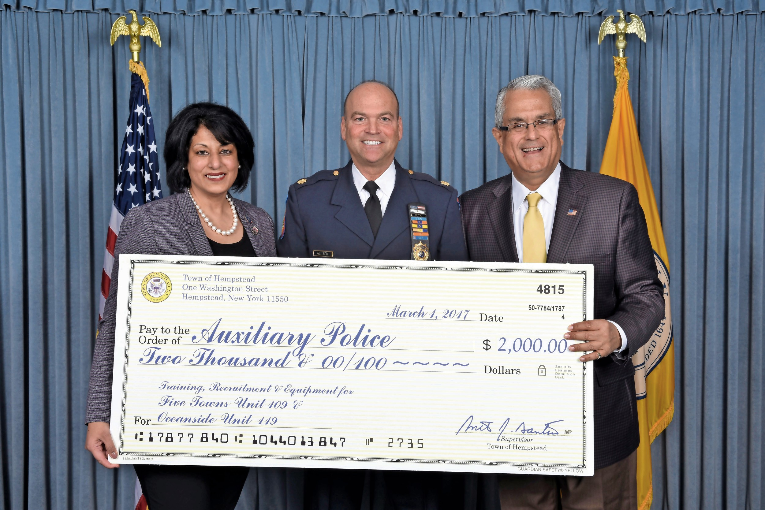 Town of Hempstead Town Clerk Nasrin Ahmad, along with Supervisor Anthony Santino, showed off a facsimile check with Deputy Inspector Danny Gluck, center, which will benefit the  auxiliary police units in the Five Towns (109) and Oceanside (119).