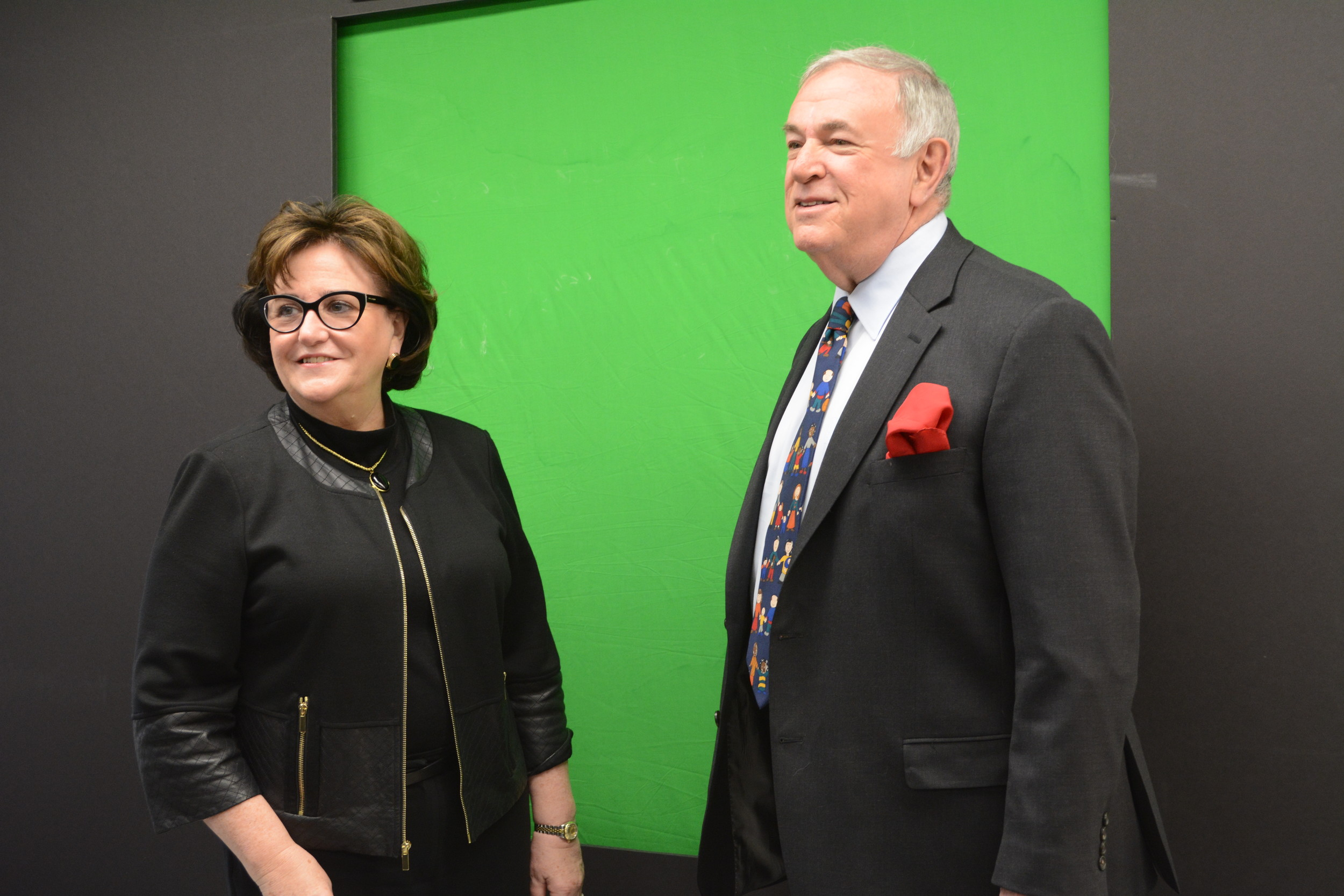 Commissioner MaryEllen Elia and Regent Roger  Tilles stood before a green screen made by students in the Global Business and Entrepreneurship Academy.
