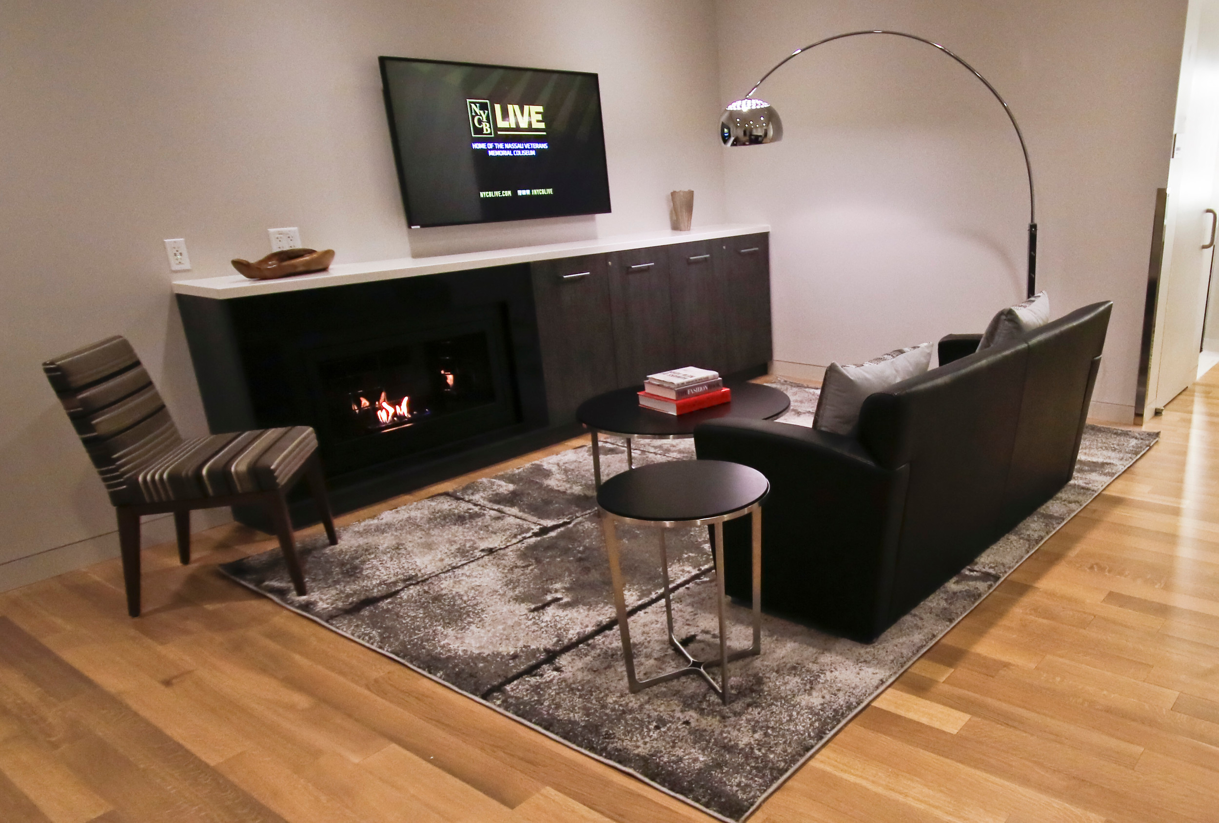 "This residential suite is designed in the ""Manhattan Modern"" style, and includes a couch, rug, fireplace and large flat screen TV"