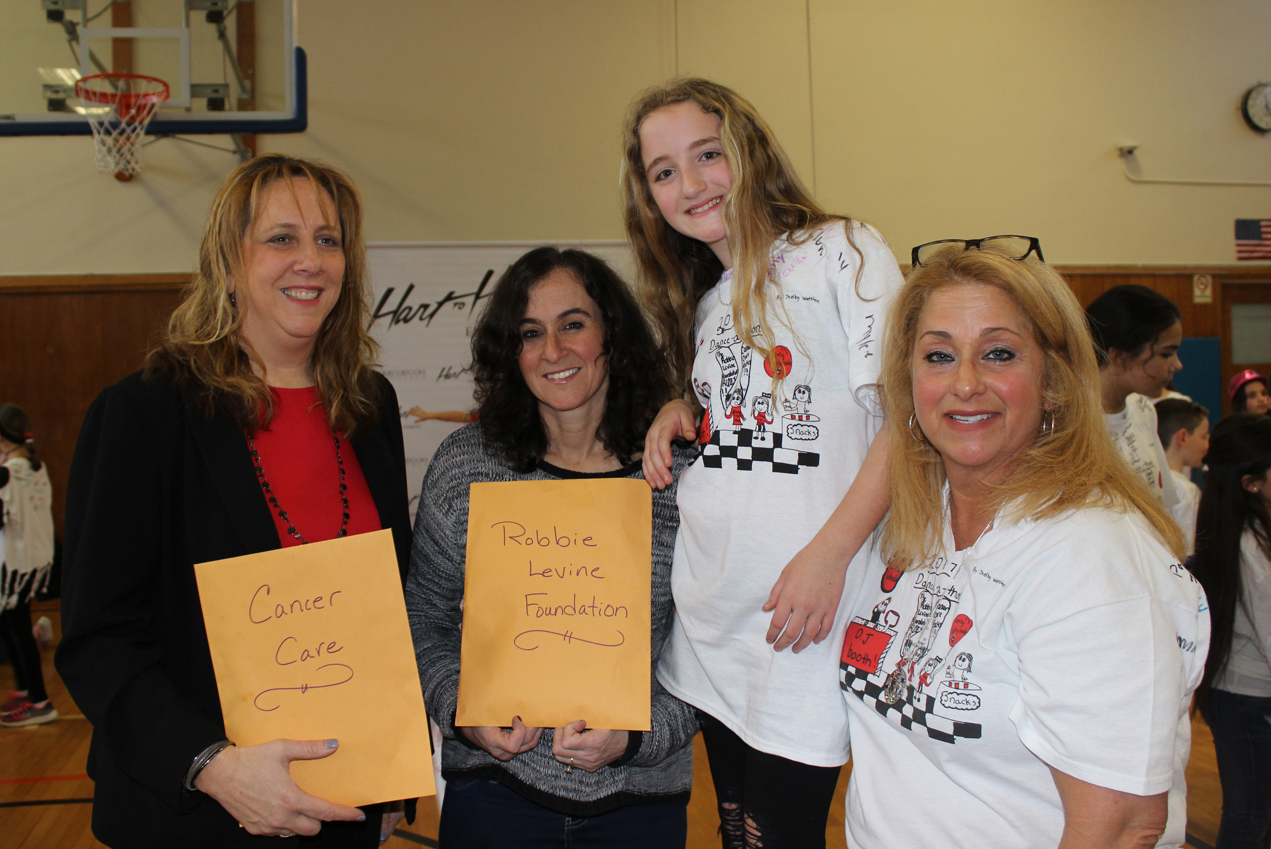 Amanda Ball, vice president of Levy-Lakeside's student countil, center right, and Soo Becchina, the student council advisor, far right, presented Tina Revelant, president of the Port Washington chapter of Cancer Care, left, and Jill Levine, founder of the Robbie Levine Foundation, with donations from the school's student body.