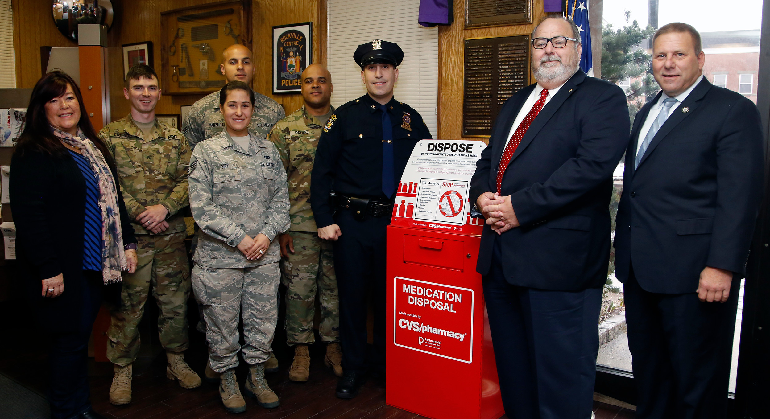 Police and community representatives show off the station's new drop-off box, which will give residents an opportunity to dispose of expired or unused medications in a safe and confidential manner.