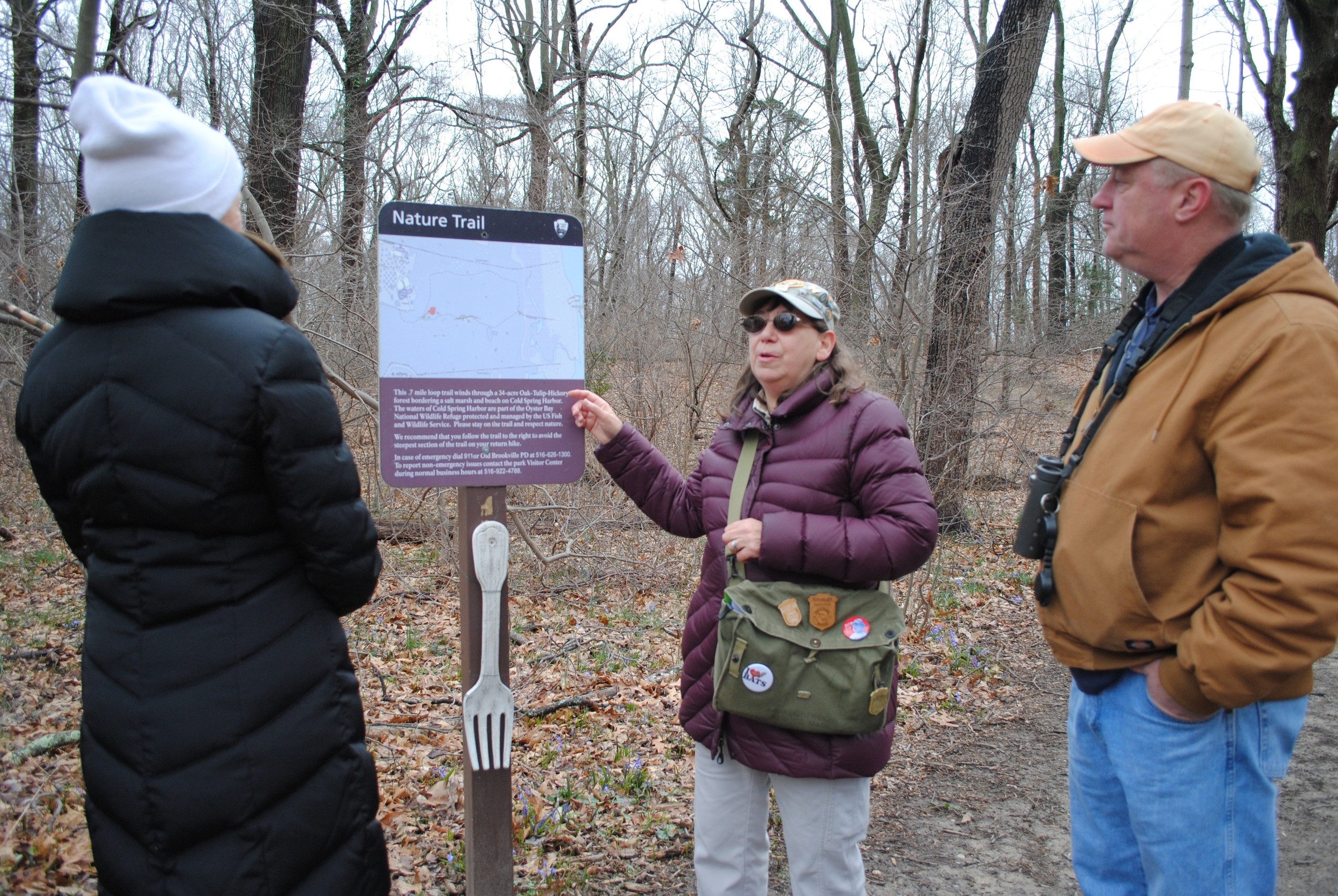 "At a ""fork in the road,"" Lois Lindberg consulted the map of the Sagamore Hill preserve with Linda Robbins and Tom Hornosky."