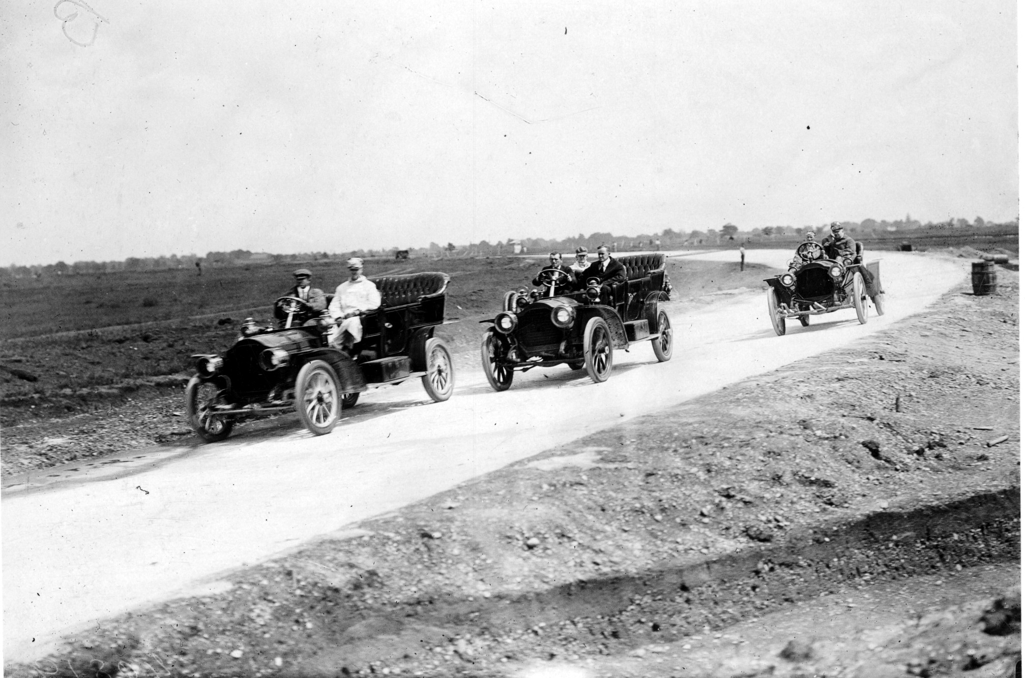 An inspection team in Packard automobiles on the Long Island Motor Parkway prior to its opening in October 1908. The photograph was taken to highlight roadway width and the banking of the road's surface — features important to the Vanderbilt Cup Races.