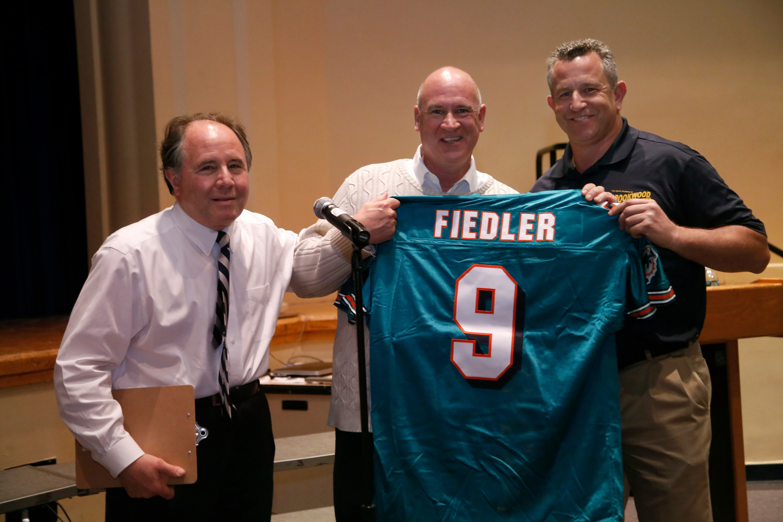 Fiedler, right, presented his Miami Dolphins jersey to his former coaches, Frank Luisi, left, and Richie Woods to be displayed in OHS's hall of fame.