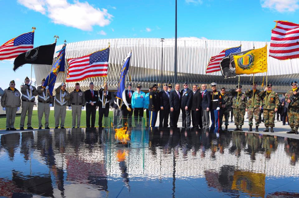 An eternal flame is part of a new memorial to military veterans at the rebuilt Nassau Veterans Memorial Coliseum. County officials, veterans and representatives from the Coliseum view the monument.