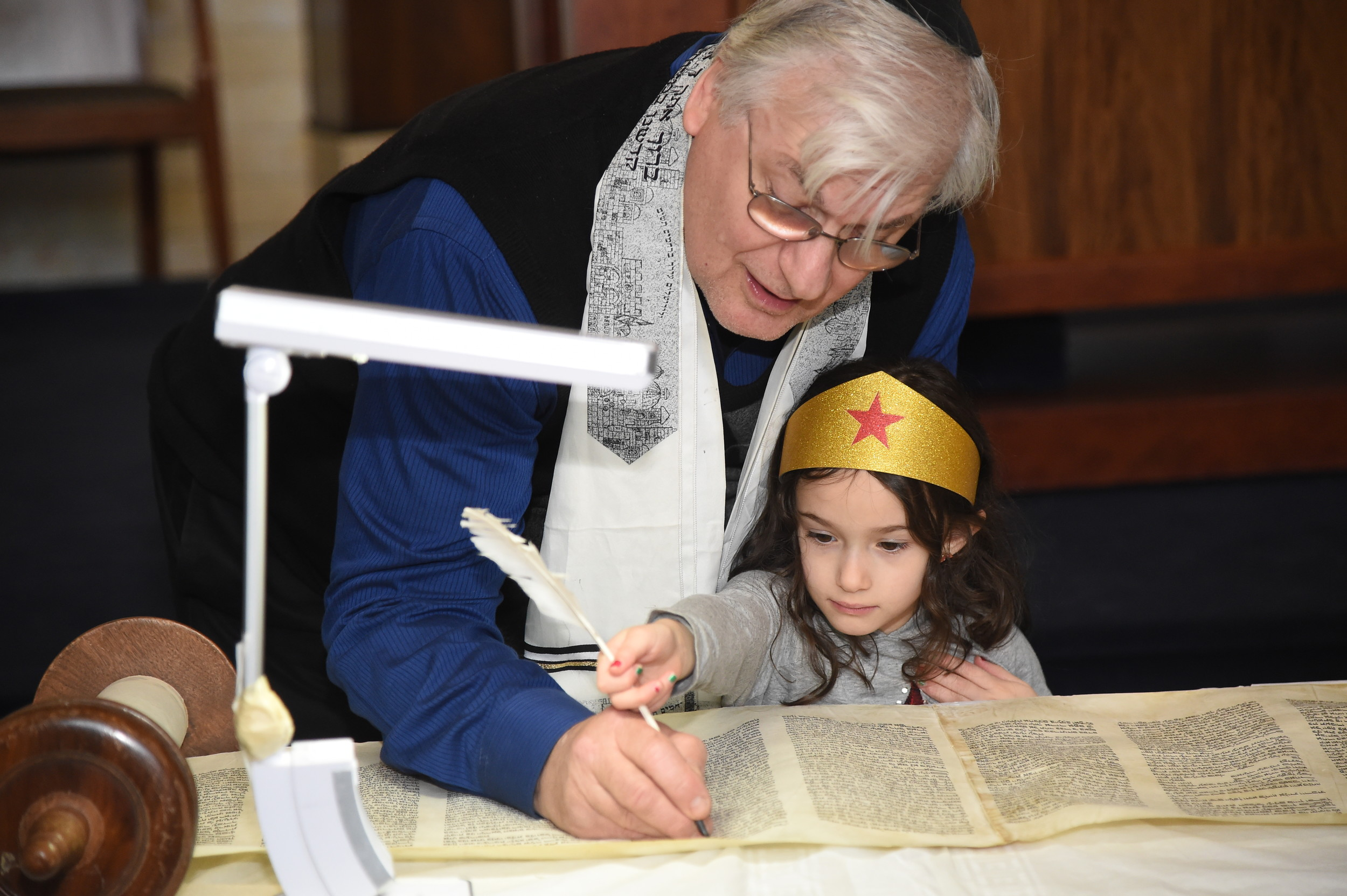 Sari Levine, 5, added a crown to her temple's Torah with the help of Master Torah Scribe Neil Yerman.