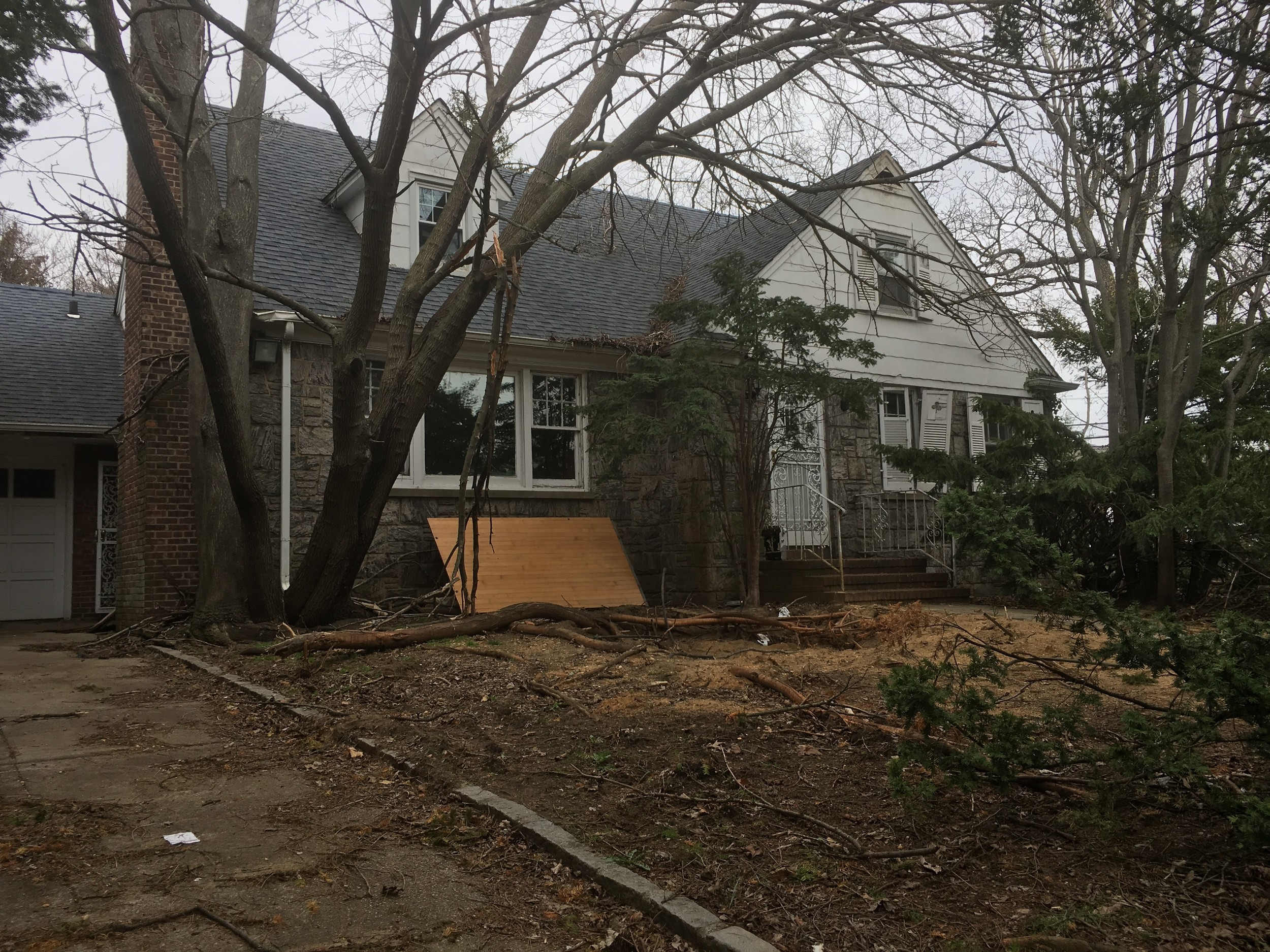 Plywood leans against the house's walls and windows are smashed at 1 Wallace Court.