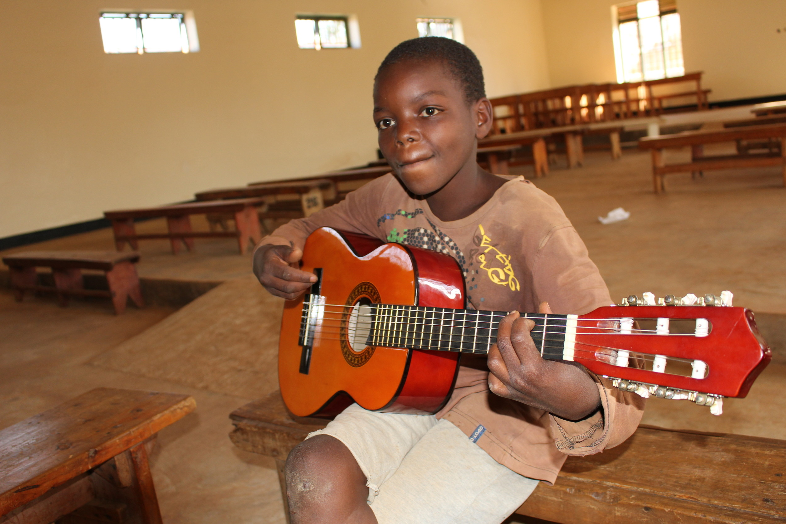 The International Sports and Music Project set up music classes at a child rehabiliatation center in Rwanda. Christopher, above, played his guitar in the class.
