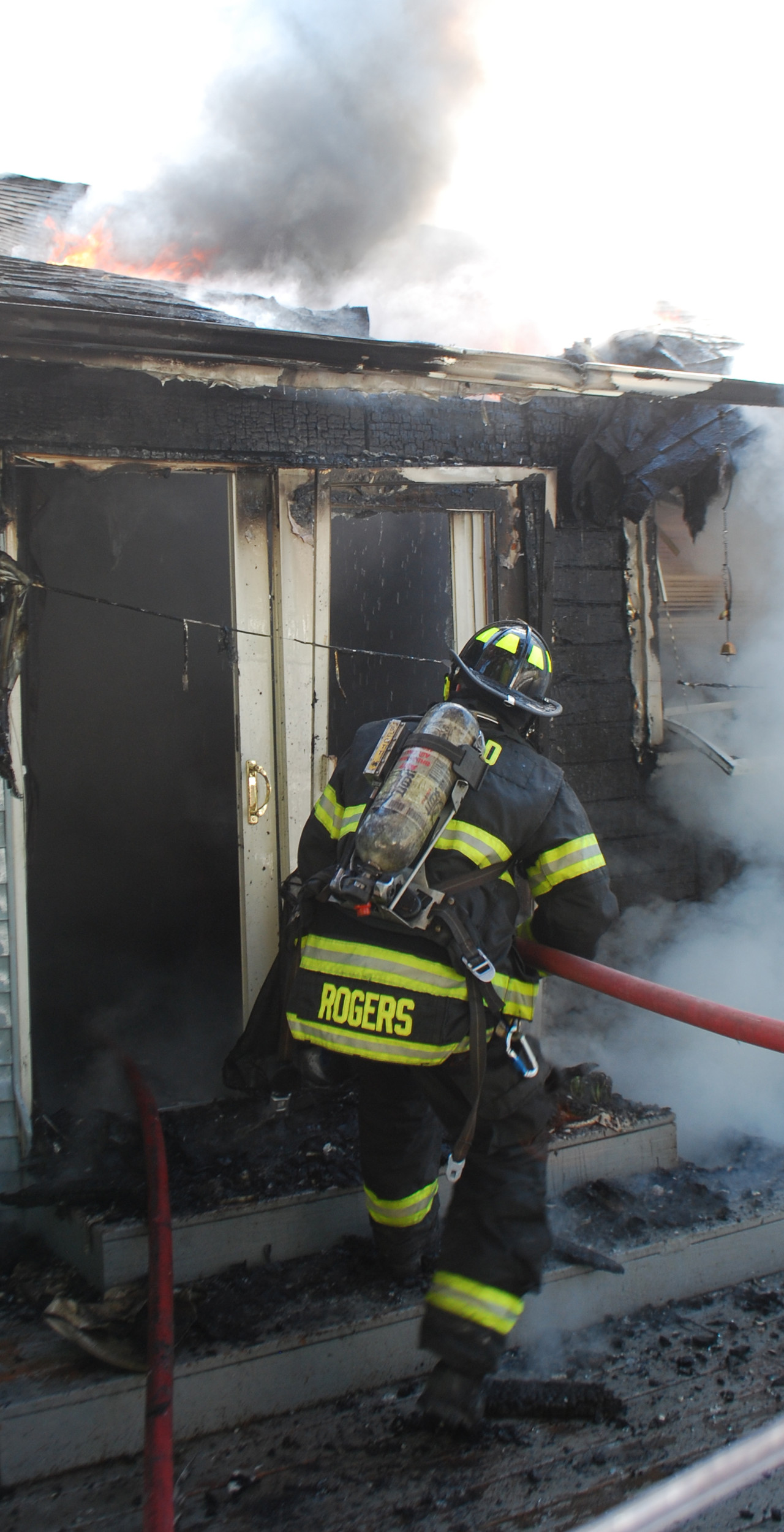 James Rogers, of the North Merrick Fire Department, fed a hose through the back of the Cosentinos' house to extinguish the flames.