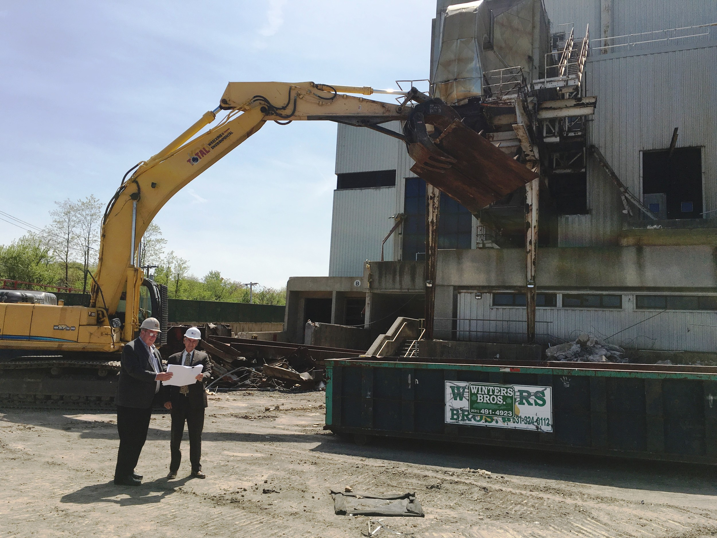 Glen Cove DPW Director Jim Byrne, left, and Mayor Spinello survey the start of the demolition of the Glen Cove Incinerator on Morris Avenue.