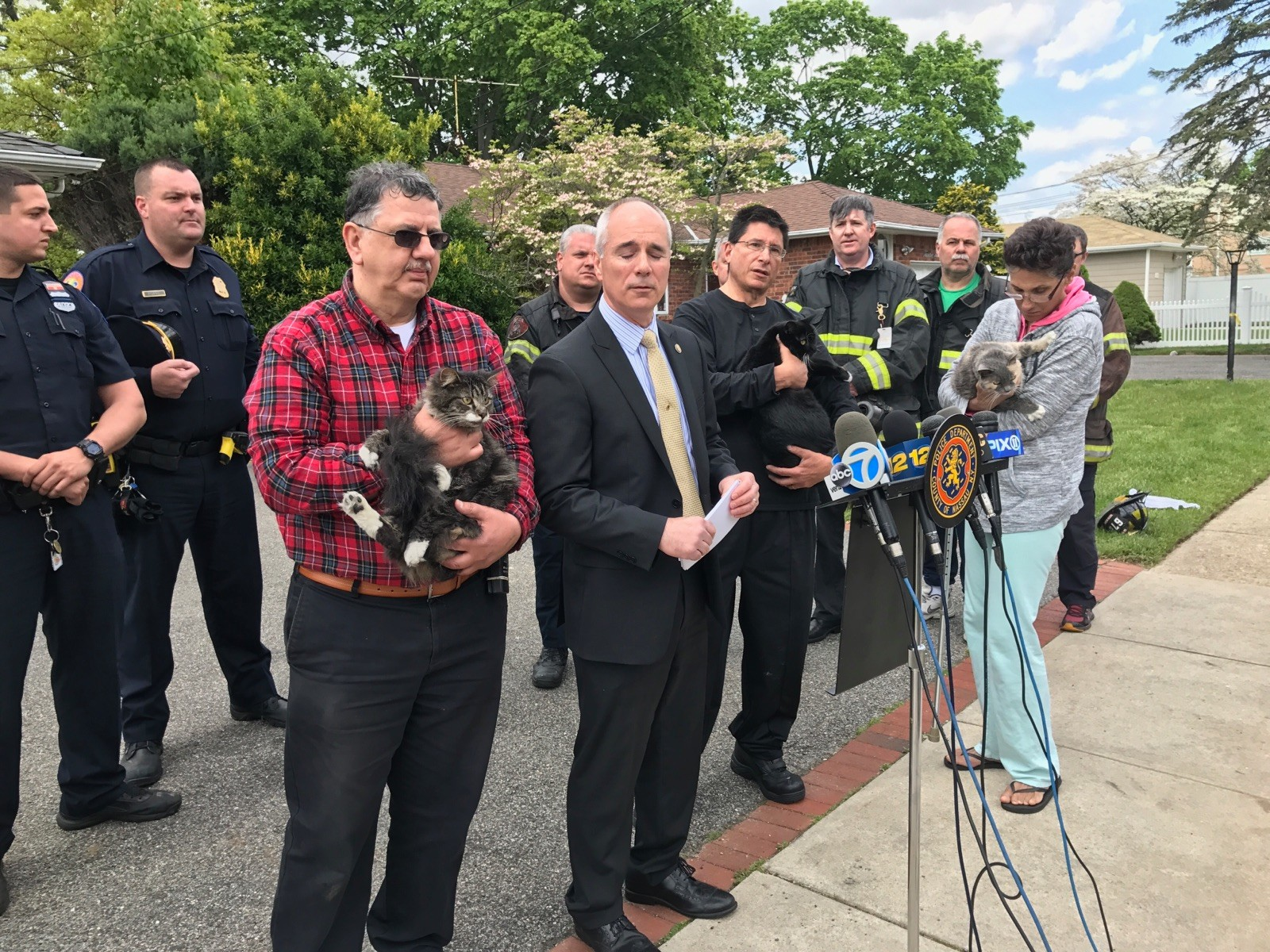 North Merrick neighbor, and member of the County Firemen's Association, John Scalesi, with cat, assisted with the rescue of several animals at the fire scene and joined members of the police and fire department at a press conference after.