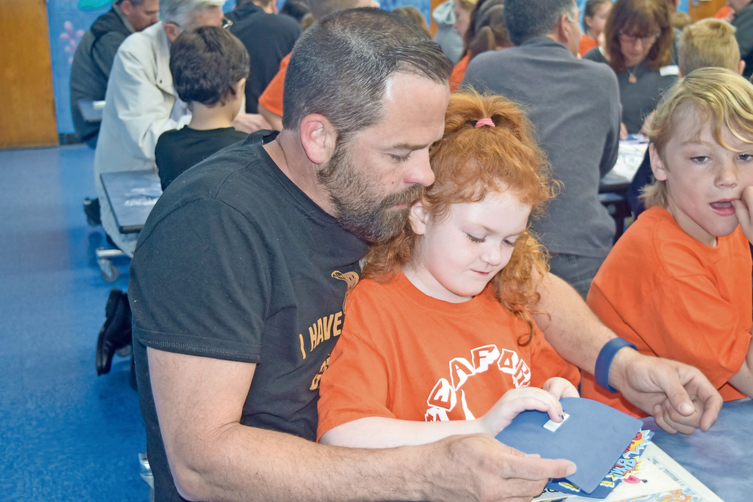 Sadie St. Pierre, 7, created a craft with her father, Charlie St. Pierre, at Harbor Elementary School's Someone Special Day on May 5.