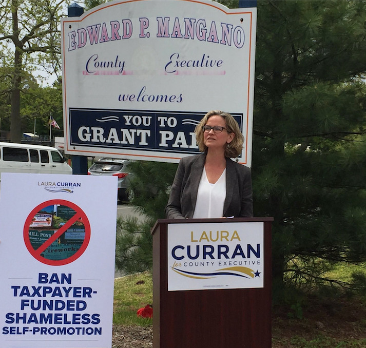 Democratic Legislator Laura Curran, of Baldwin, continued her campaign for county executive in Hewlett last week, where she blasted the numerous signs and other pieces of county property bearing the name of Ed Mangano, current county executive.