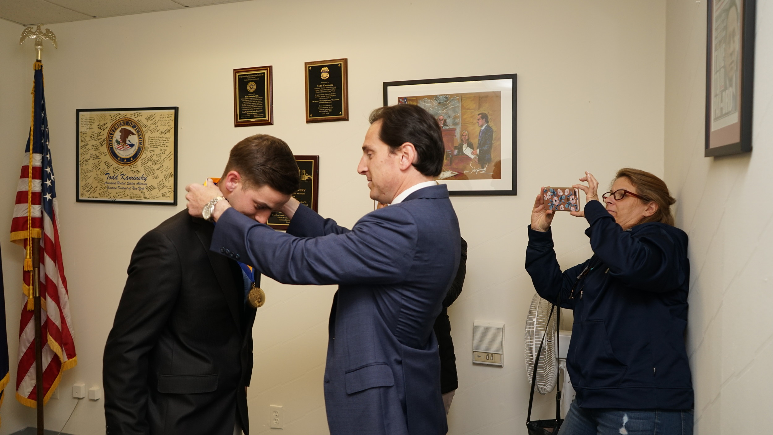 Tyler Ostrander, left, before receiving a Liberty Medal from State Sen. Todd Kaminsky. The young man saved Long Beach resident Joyce Coletti, center, from choking at Jimmy Hays Steakhouse in Island Park last month.