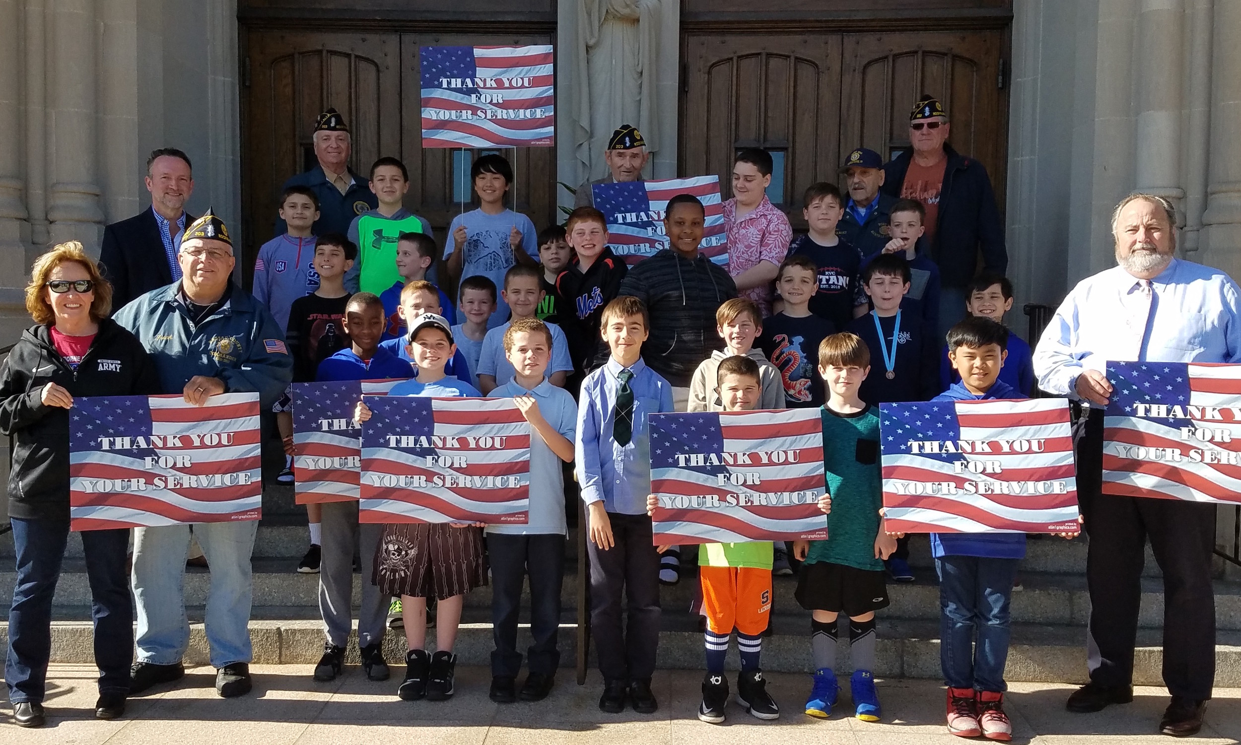 With the help of veterans and village officials, members of the St. Agnes Cathedral Boys Choir proudly displayed their patriotic lawn signs in front of the church on Monday.