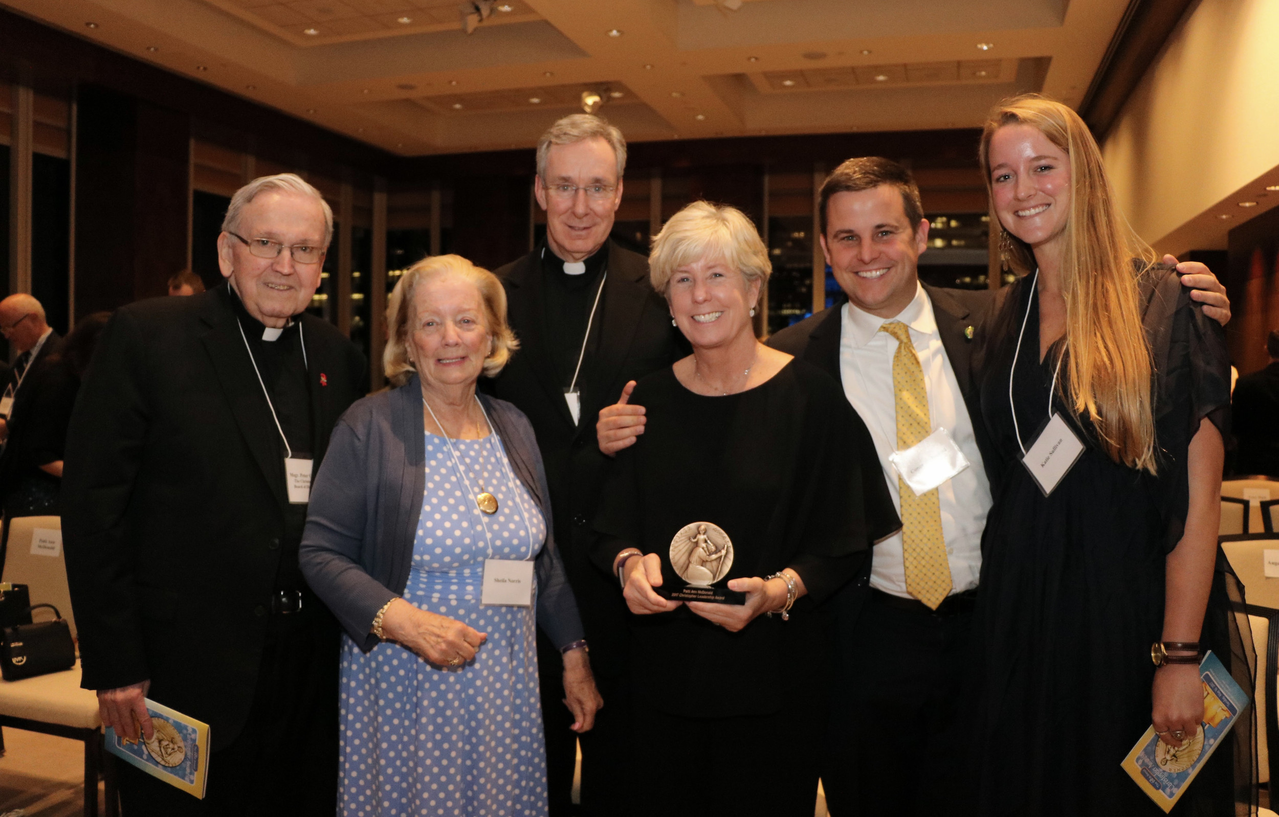 McDonald with her family and friends after the ceremony. From left are Monsignor Peter Finn, Sheila Norris, Rev. Peter Le Jacq, NYPD Sgt. Conor McDonald and his girlfriend Katie.