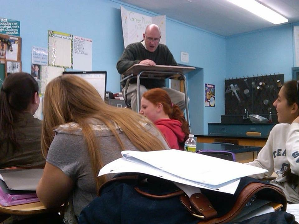 Woods often relied on oddball ways to get students engaged in class. Here he is sitting and reading at a desk on top of a desk.