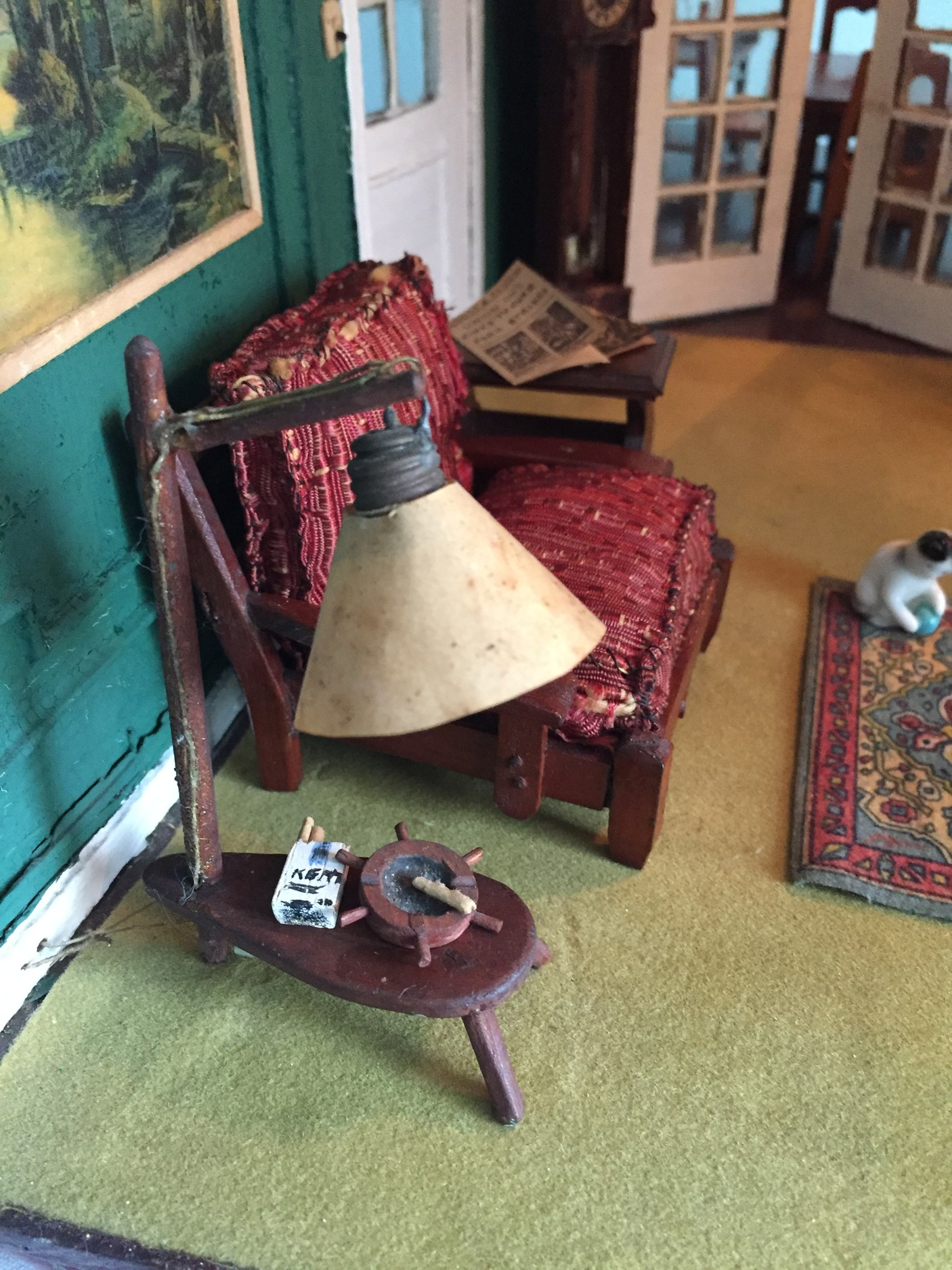 In the downstairs living room, there is a pack of smokes and an ashtray on a table with a working lamp. In the back stands a grandfather clock and one pair of French doors that lead into a dining area.