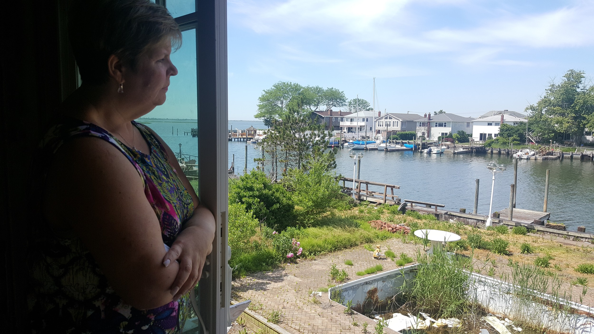 Illona Jagnow, a Freeport native, looked out the patio window of her family home off South Long Beach Avenue at an unruly yard covered in weeds and construction debris.