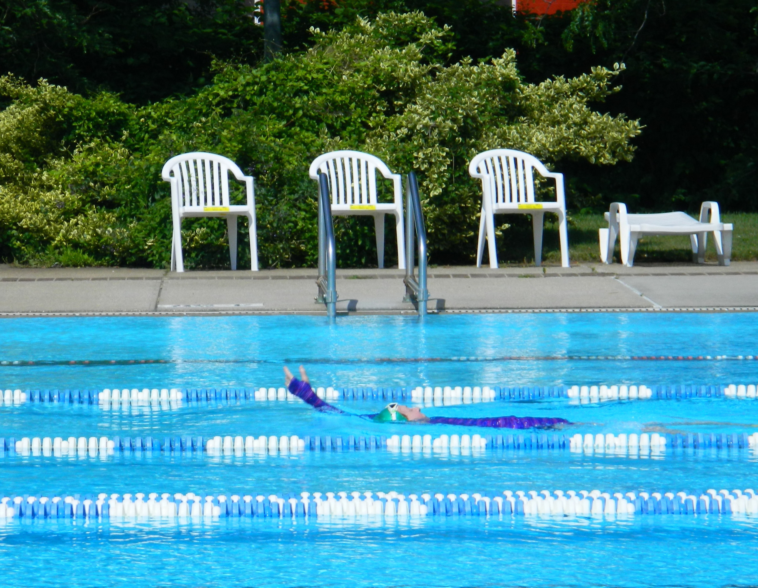 the olympic sized pool glimmered under sunlight while a woman a freeport woman enjoyed