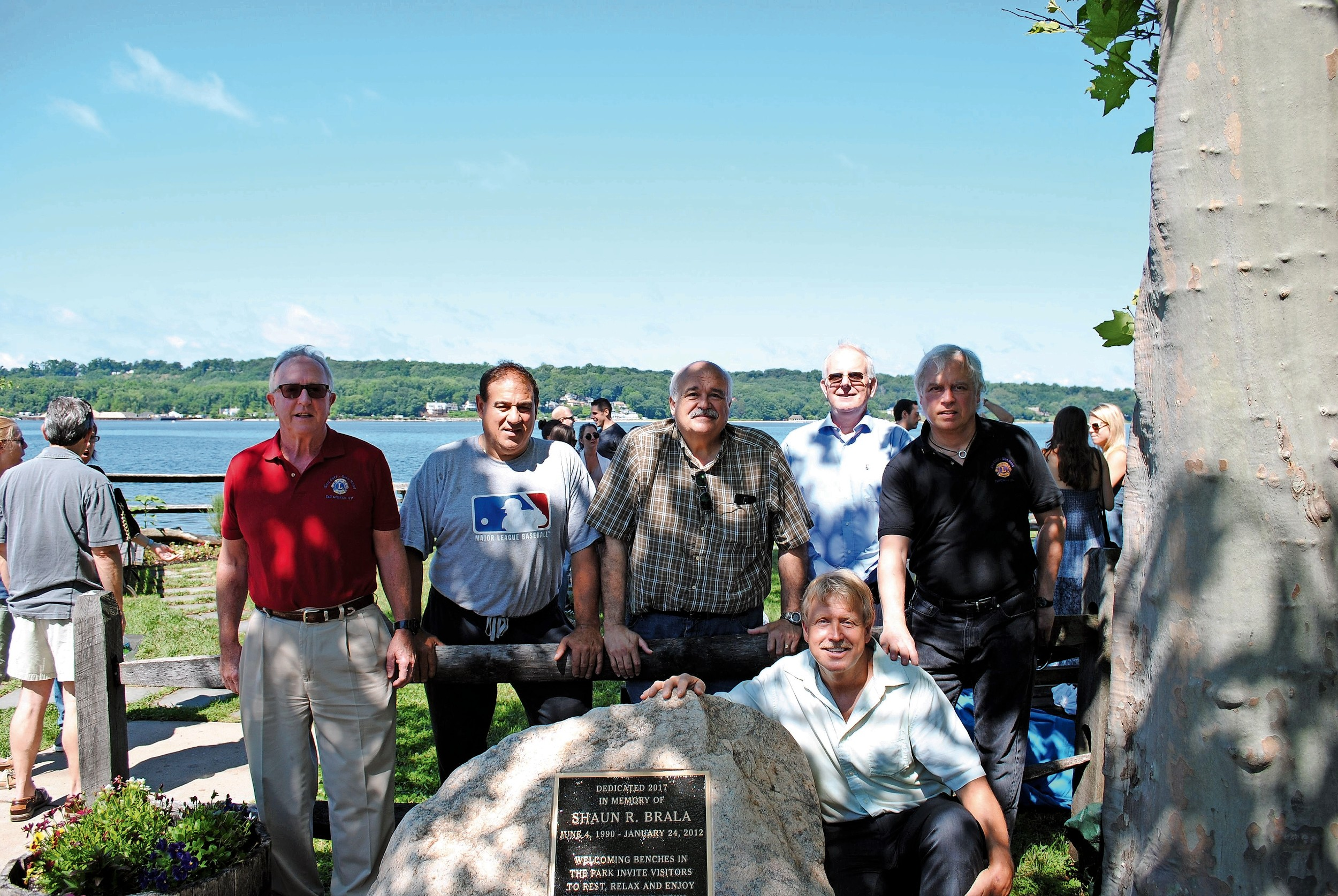 Members of the Sea Cliff-Glen Head Lions Club with John Brala during his son's plaque unveiling at Rum Point Park.