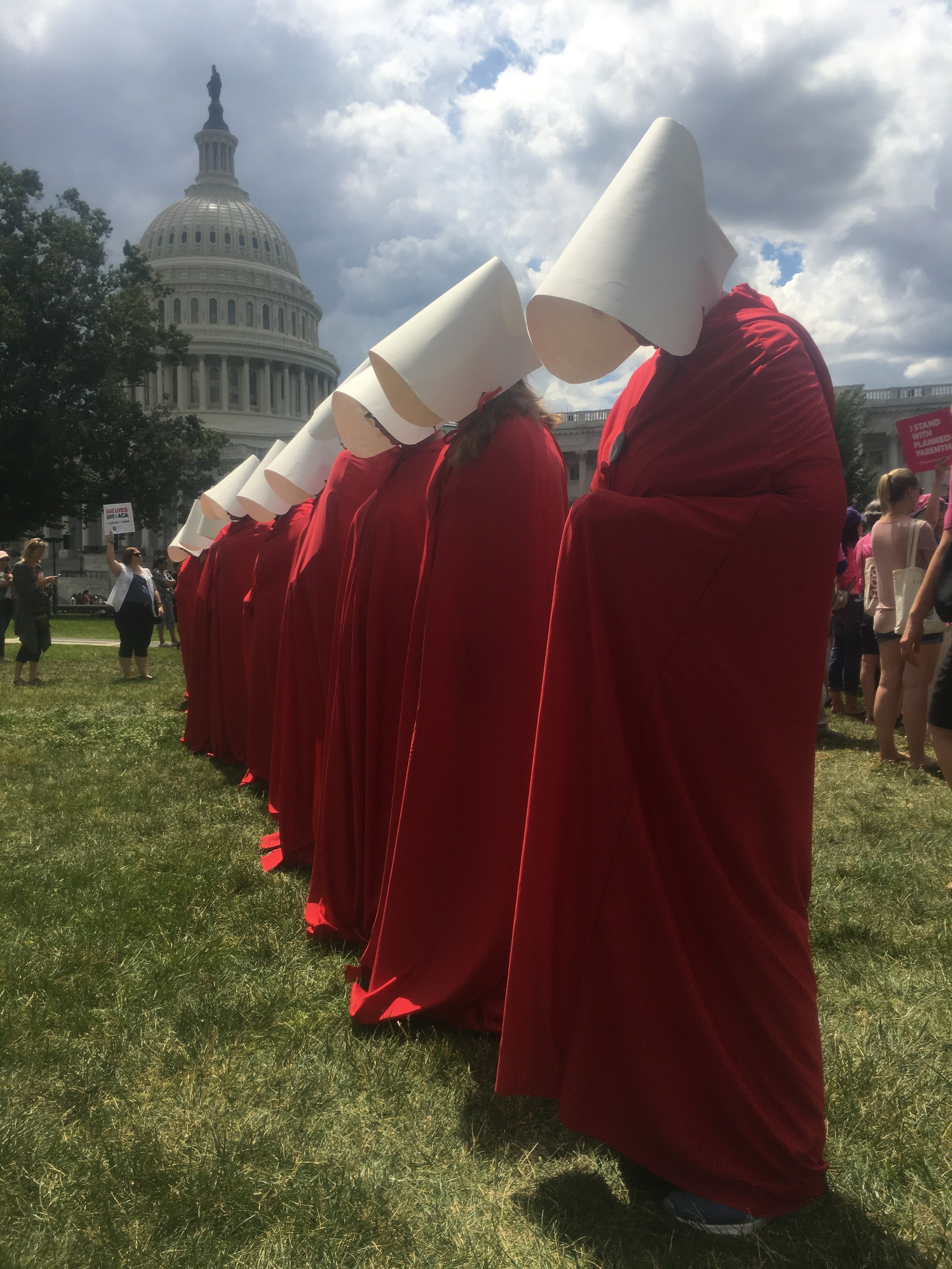 "lanned Parenthood volunteers donned outfits worn by a fictional caste of women forced into sexual servitude in Margaret Atwood's dystopian novel ""The Handmaid's Tale,"" at a rally in the capital."