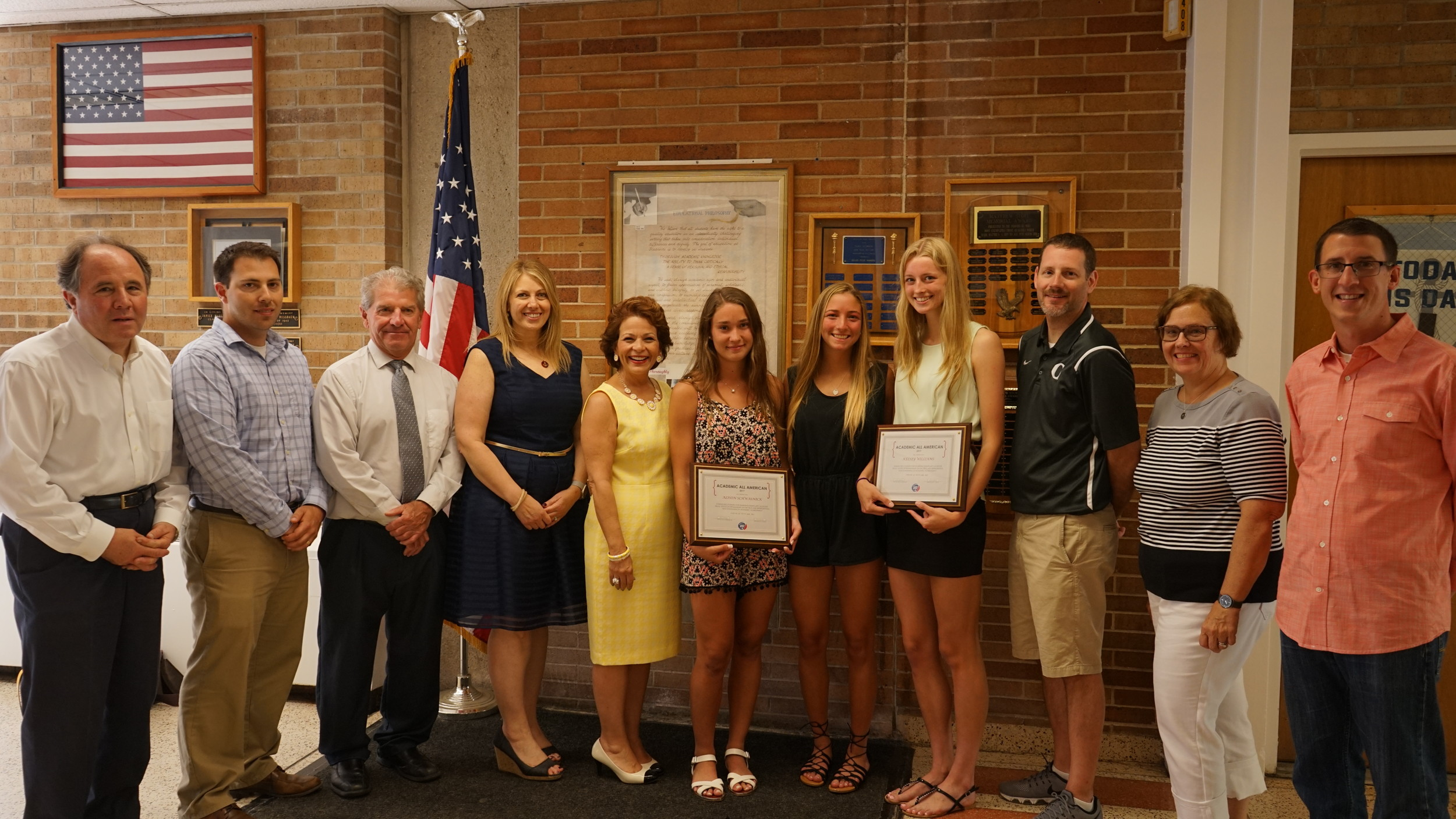 Alison Schwasnick, sixth from left, Christina McCabe and Kelsey Williams, with Frank Luisi, advisor for NCAA college-bound student athletes, left, guidance counselor John Madden, Jeff Risener, director of physical education, health and athletics, Assistant Superintendent Diane Provvido, School Superintendent Dr. Phyllis S. Harrington, former girls lacrosse coach Kenneth Dwyer, and guidance counselors Michele Mellilo and Kevin Carbonetti.