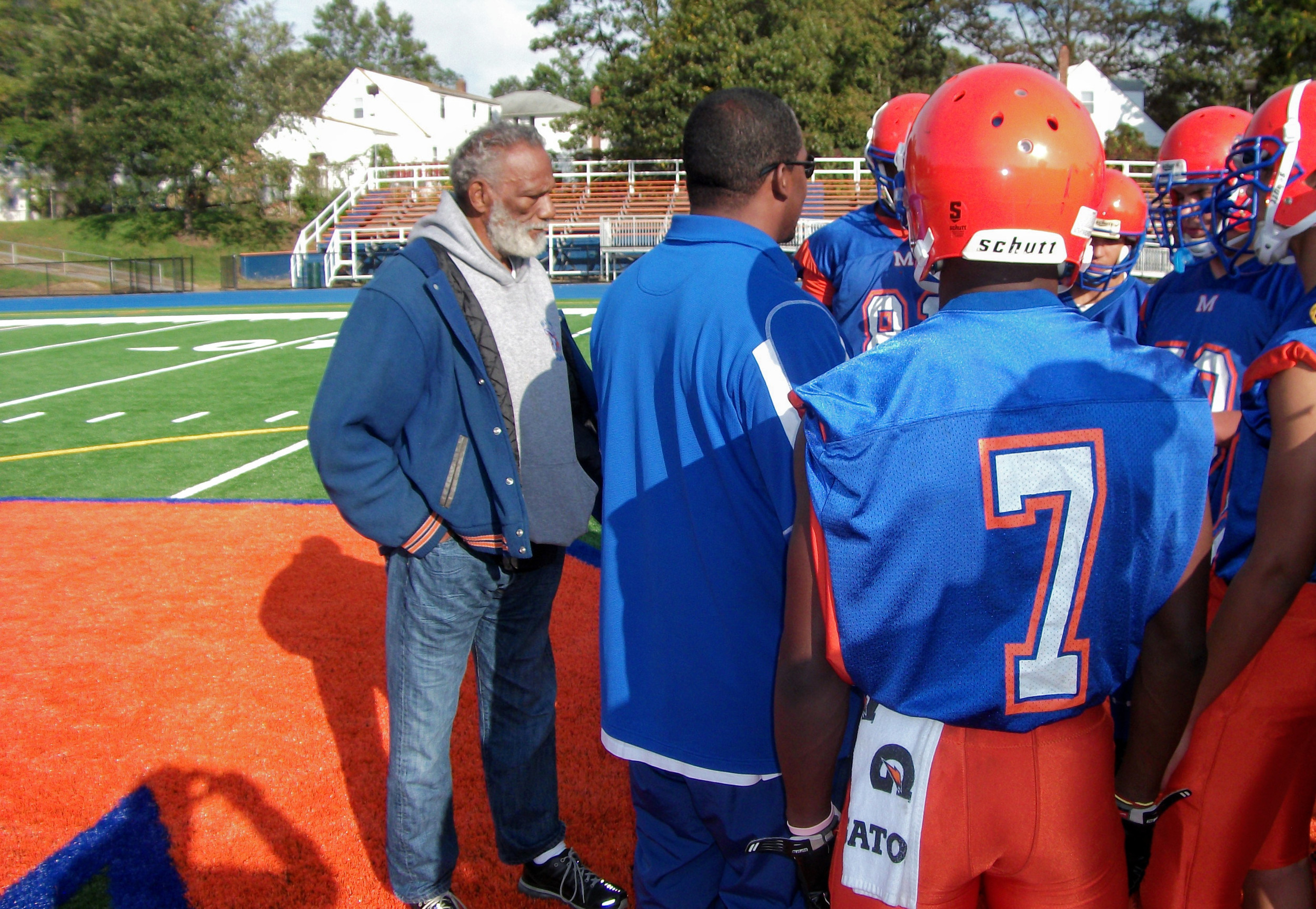 Colbert Britt, far left, with Malverne High School football players on the field that will soon bear his name.