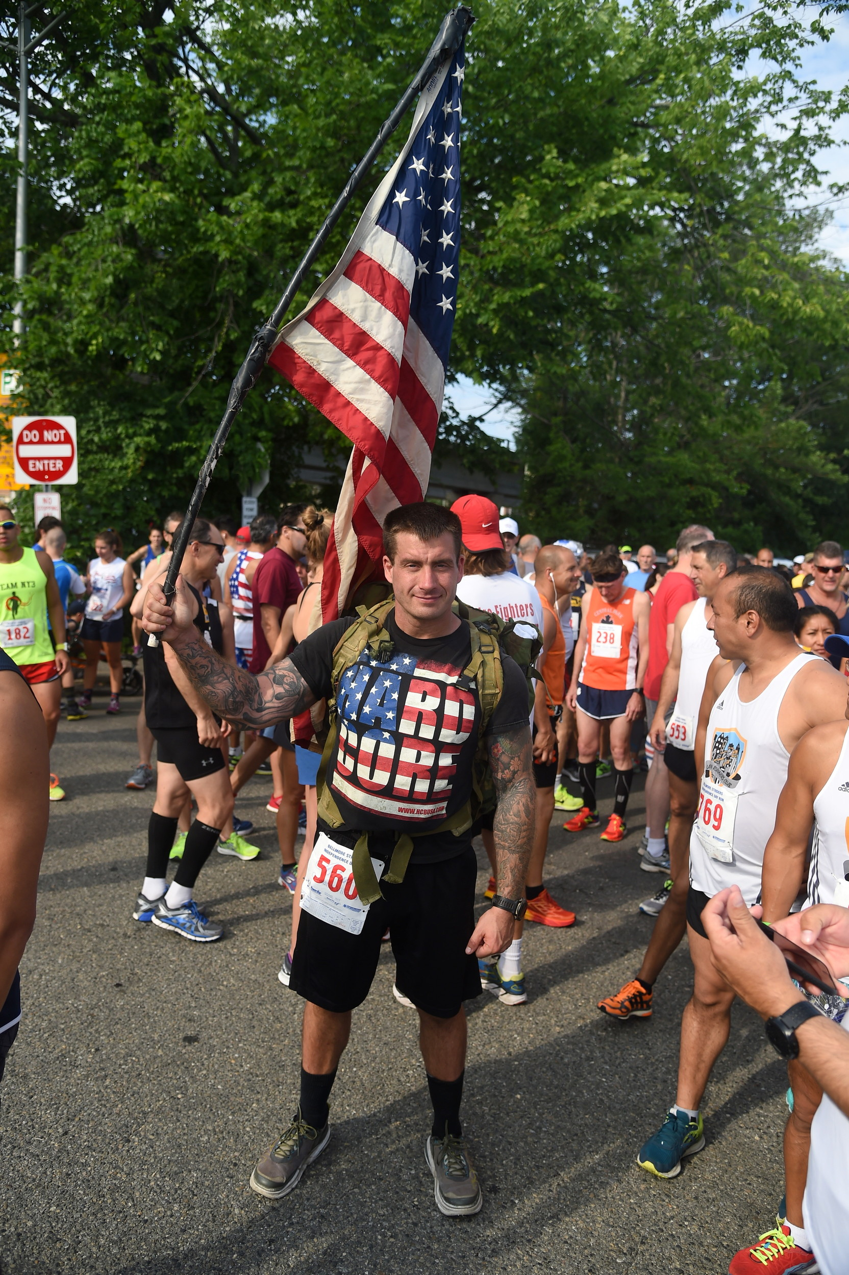 Billy Richards, a U.S. Marine from Islip, hoisted the flag before the kick-off of the Independence Day run.