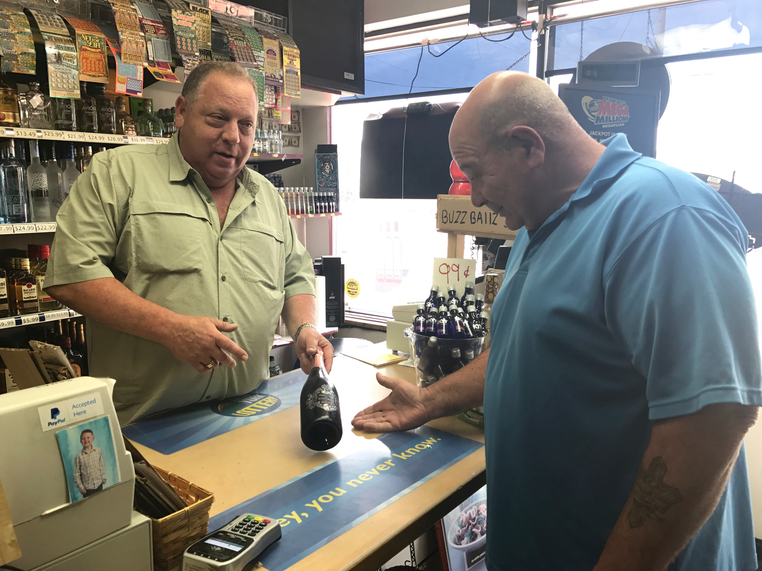 Peninsula Wines owner James Cari, left, discussed the texture of this rosé with store employee Frank Garraputa.