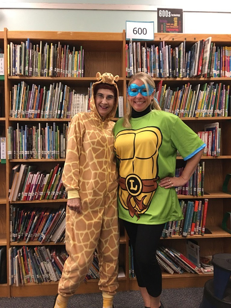 Susman, left, wore her giraffe onesie on Halloween. Her colleague at East Lake Elementary School, Lisa Gennardo, and her students know about her collection.