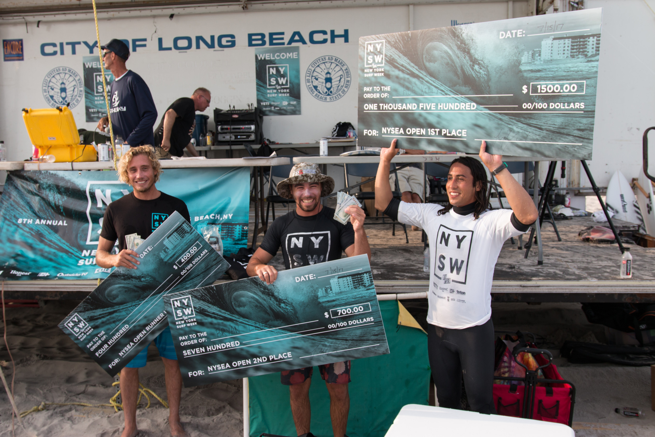 The three winners of the open surf contest collected their winnings on July 15. Leif Engstrom, left, won third place, while Bryan Laide won second place and Rob Kelly took first.