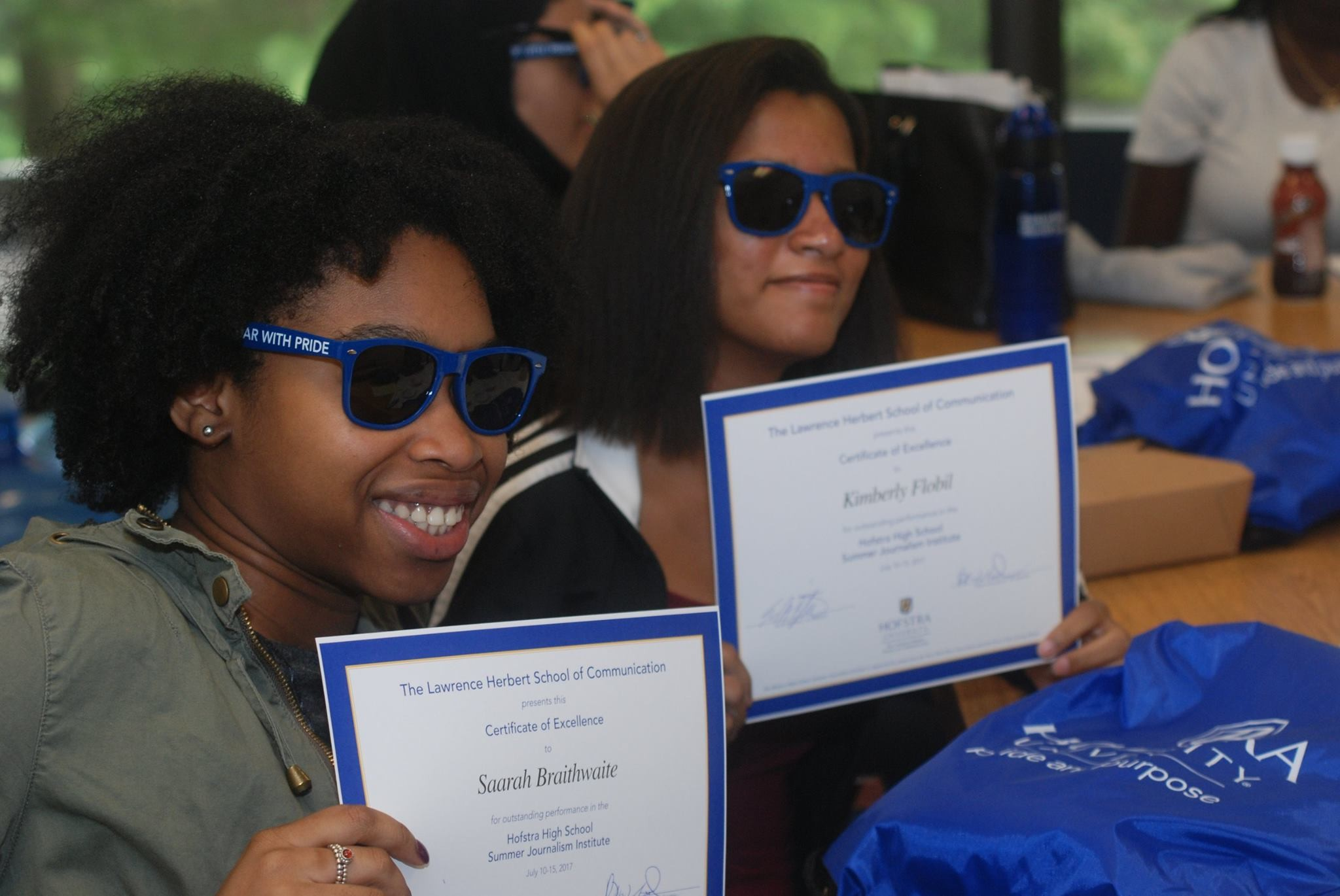 Saarah Braithwaite, left, and Kimberly Flobil, both of Elmont High School, showed off their certificates and Hofstra University gear after recently completing the High School Summer Journalism Institute.