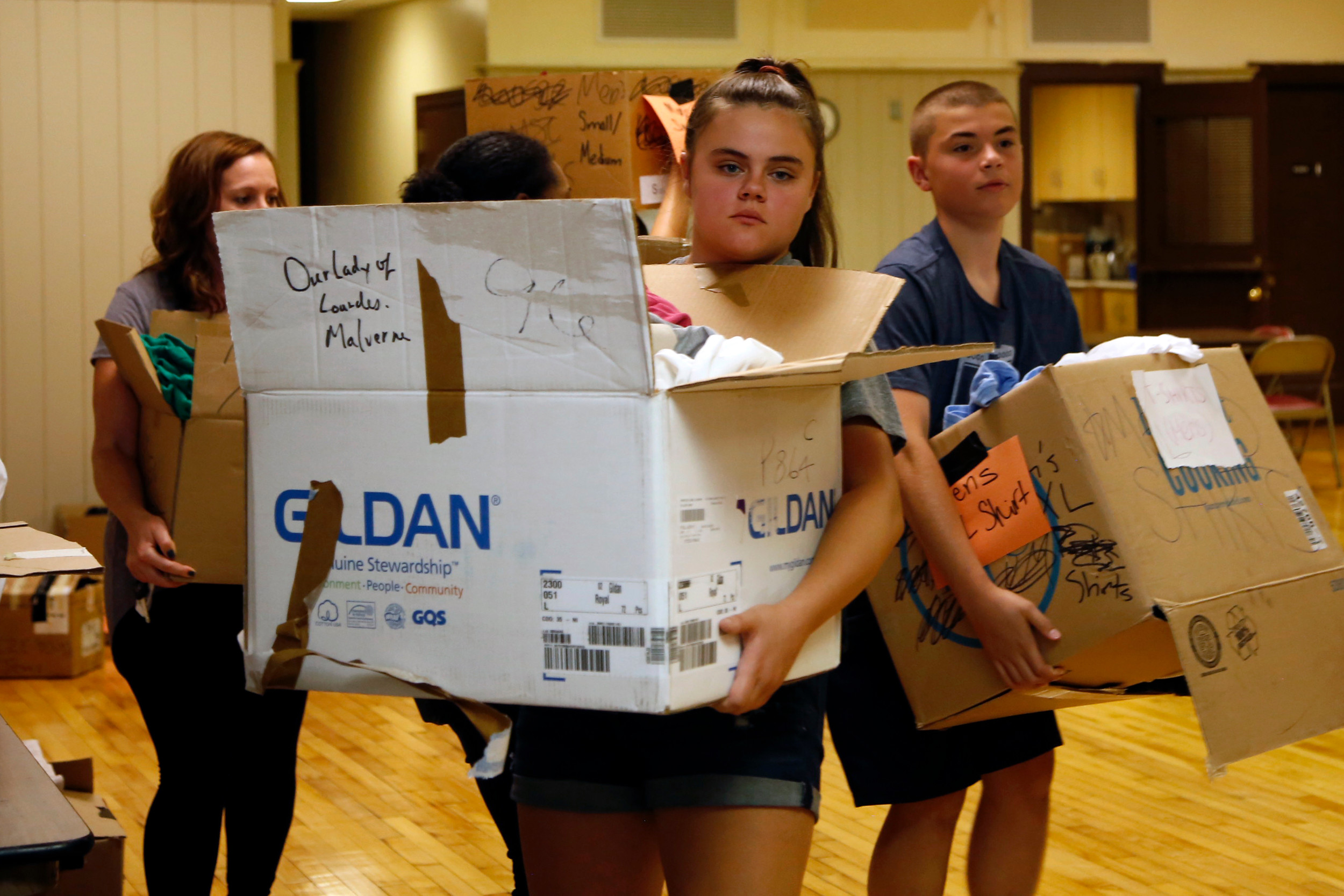 Gwen Church and TJ Ledwith carried boxes of supplies to the caravan.