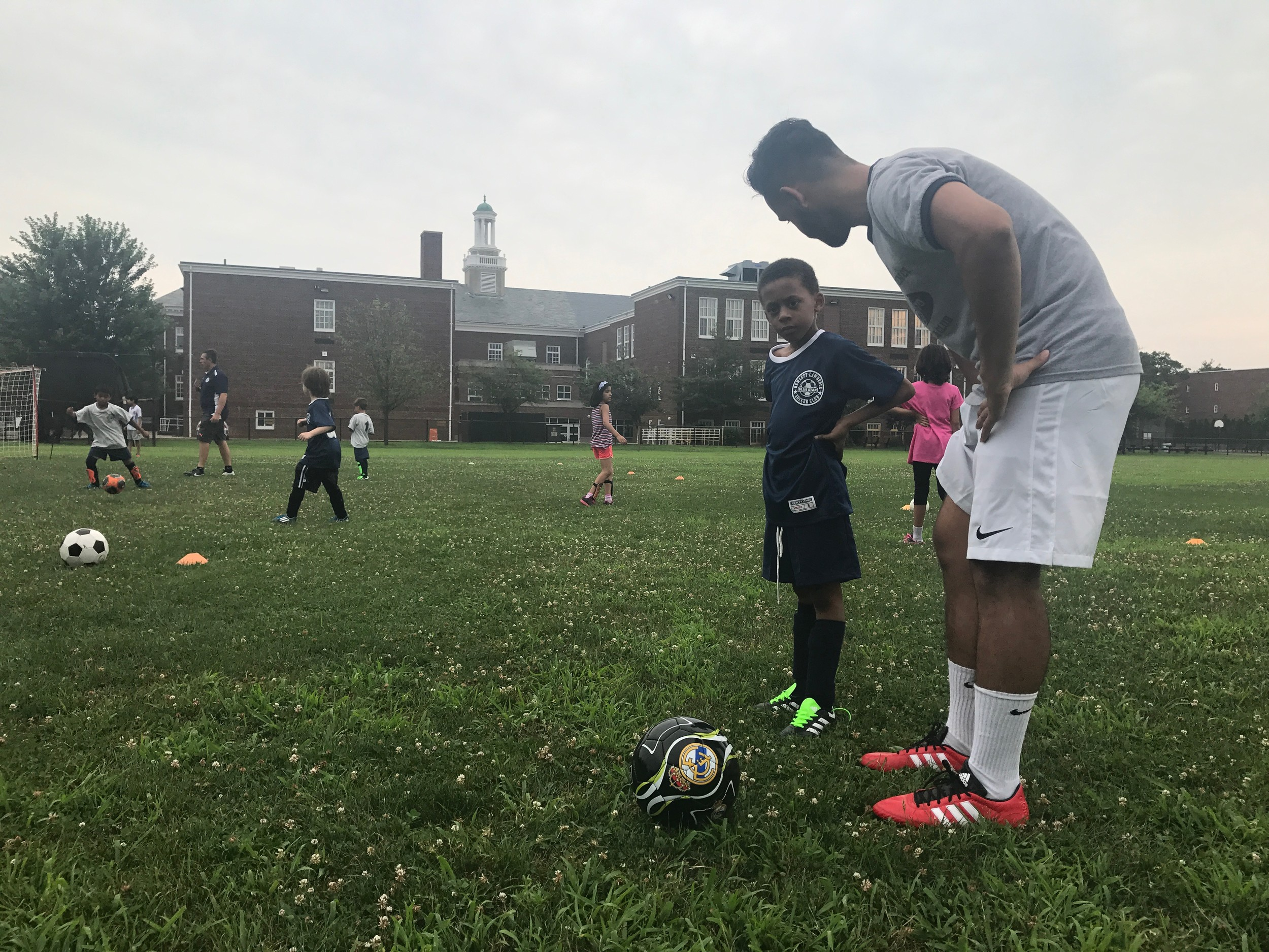 David Ramirez, who will be playing for Queens College this fall gave Roddy Perard, 6, advice on his passing technique.
