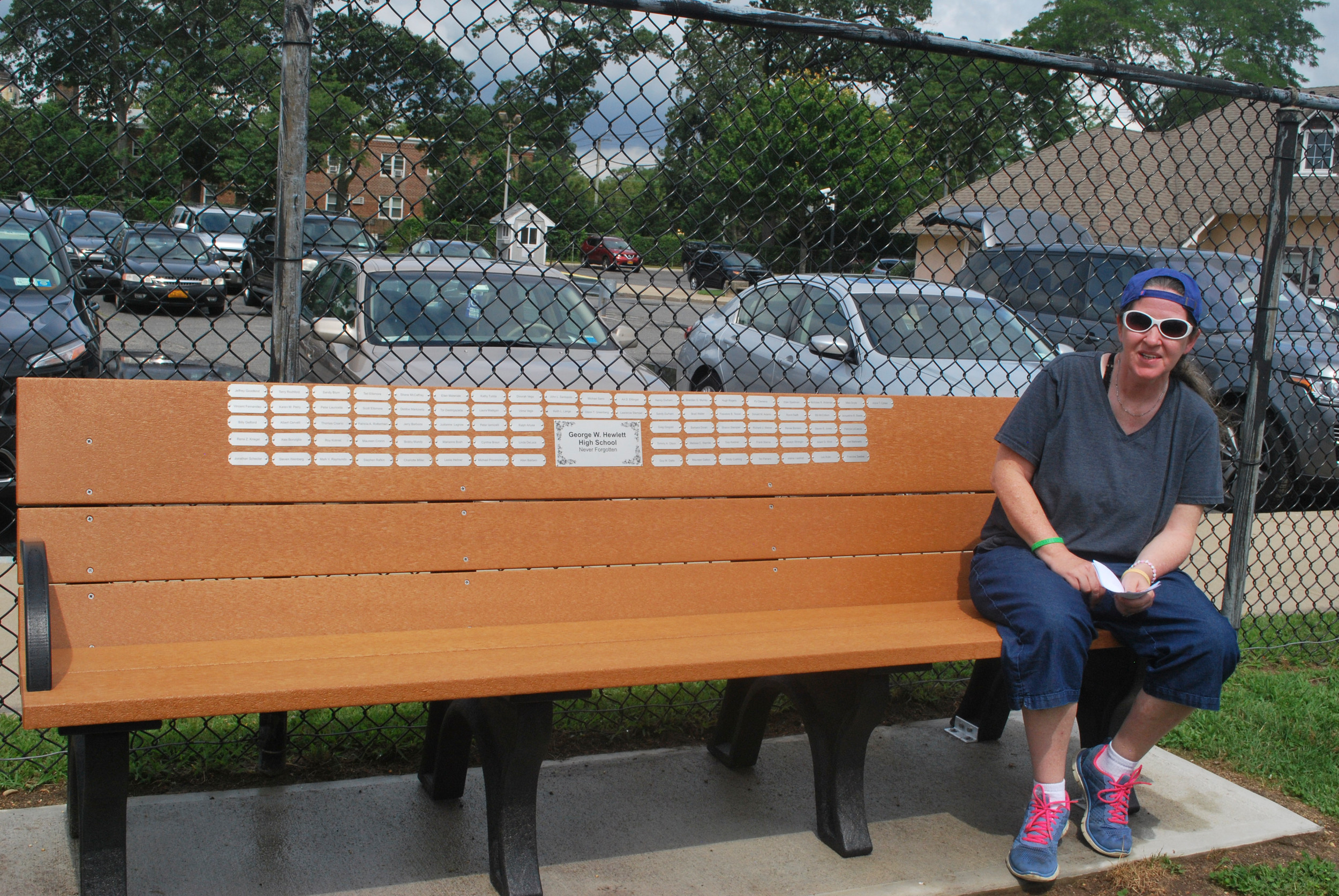 Hewlett High School Never Forgotten creator Patty O'Donnell Proppe on the bench she and her fellow Breakfast Club members dedicated to alums who died.