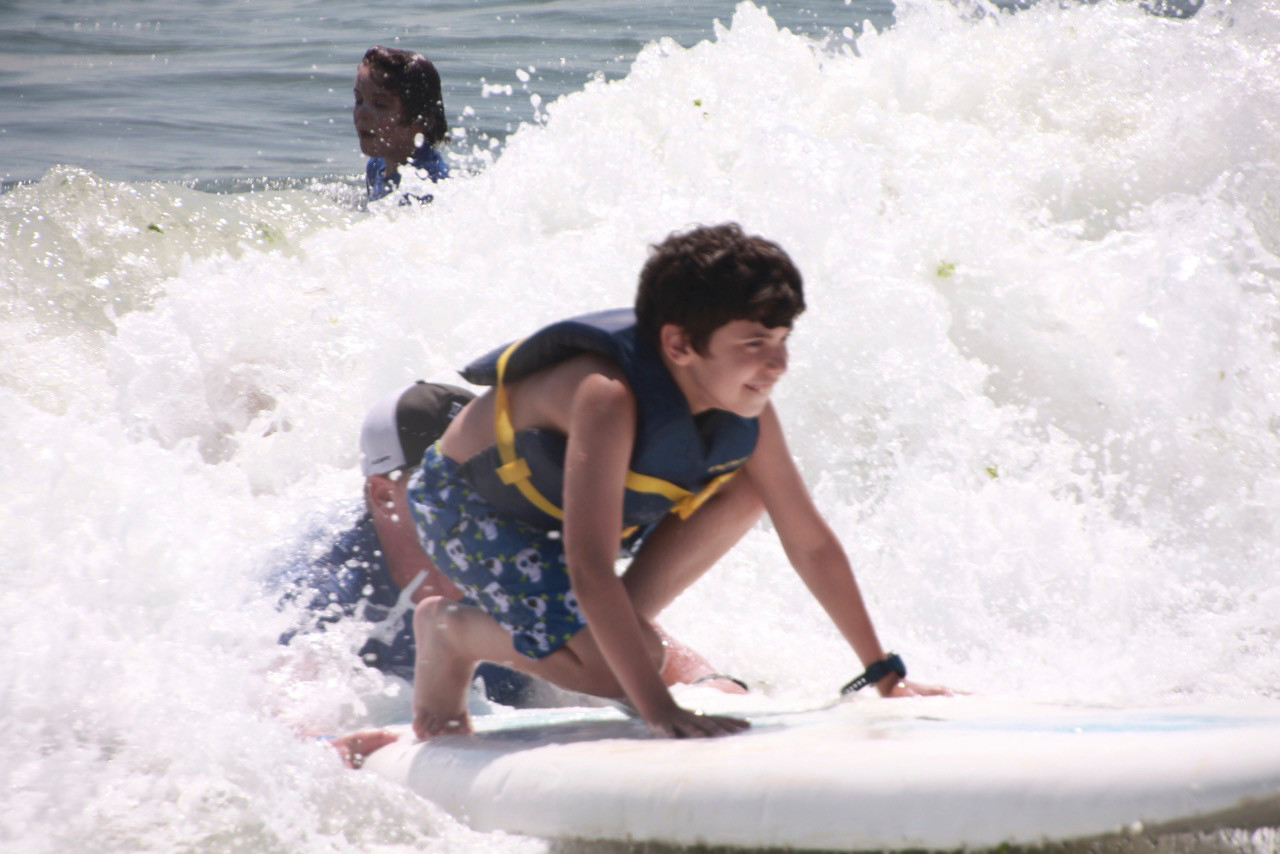 Gural JCC Camp Friendship camper Domenic D'Arcio, learning to surf in Long Beach, leaned into his stance as a wave hit his board on July 31.