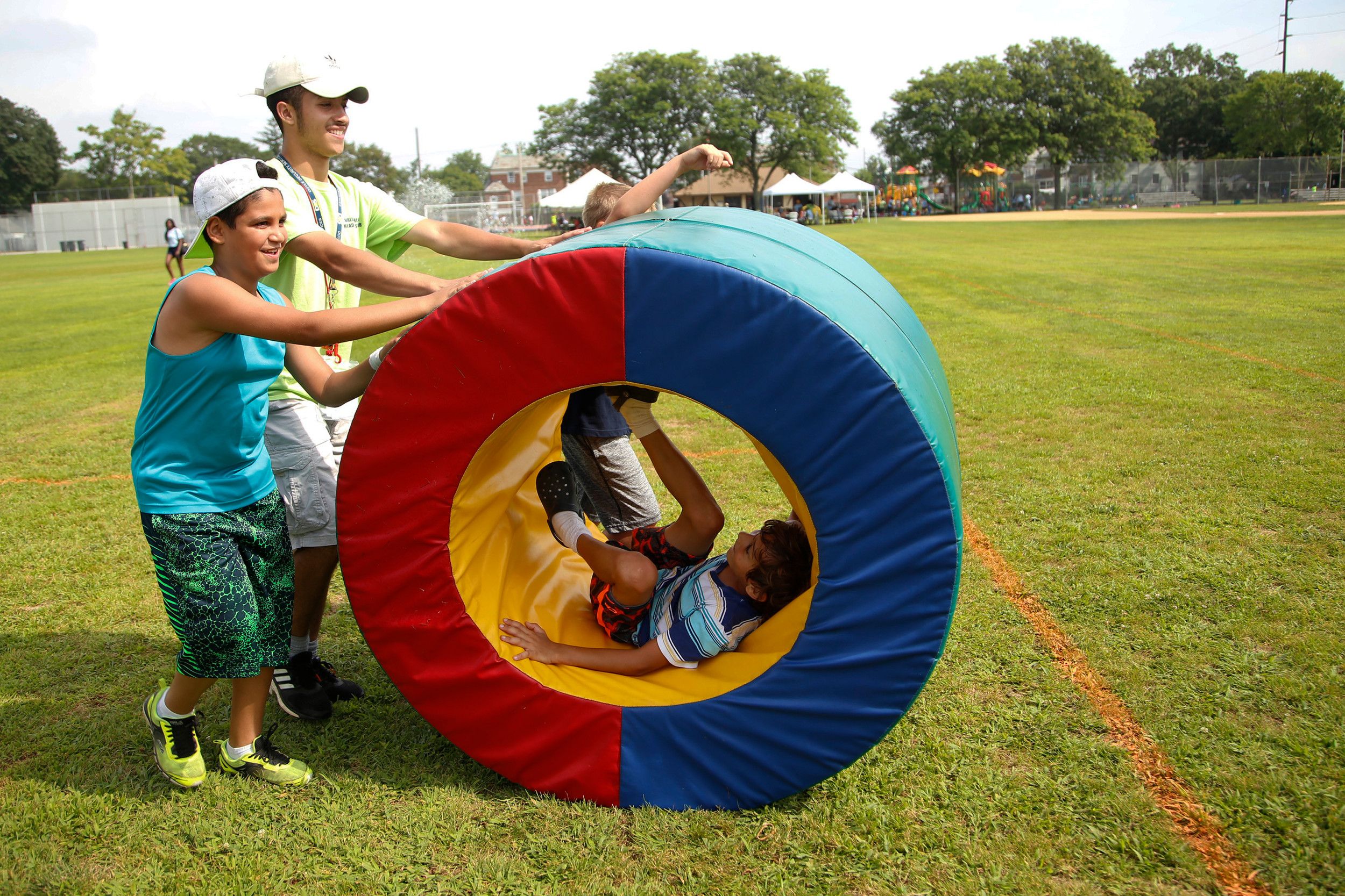Counselor Melvin Fuentes and Ebraam Abdou, 9, rolled Rafael Liranzo, 8, around.