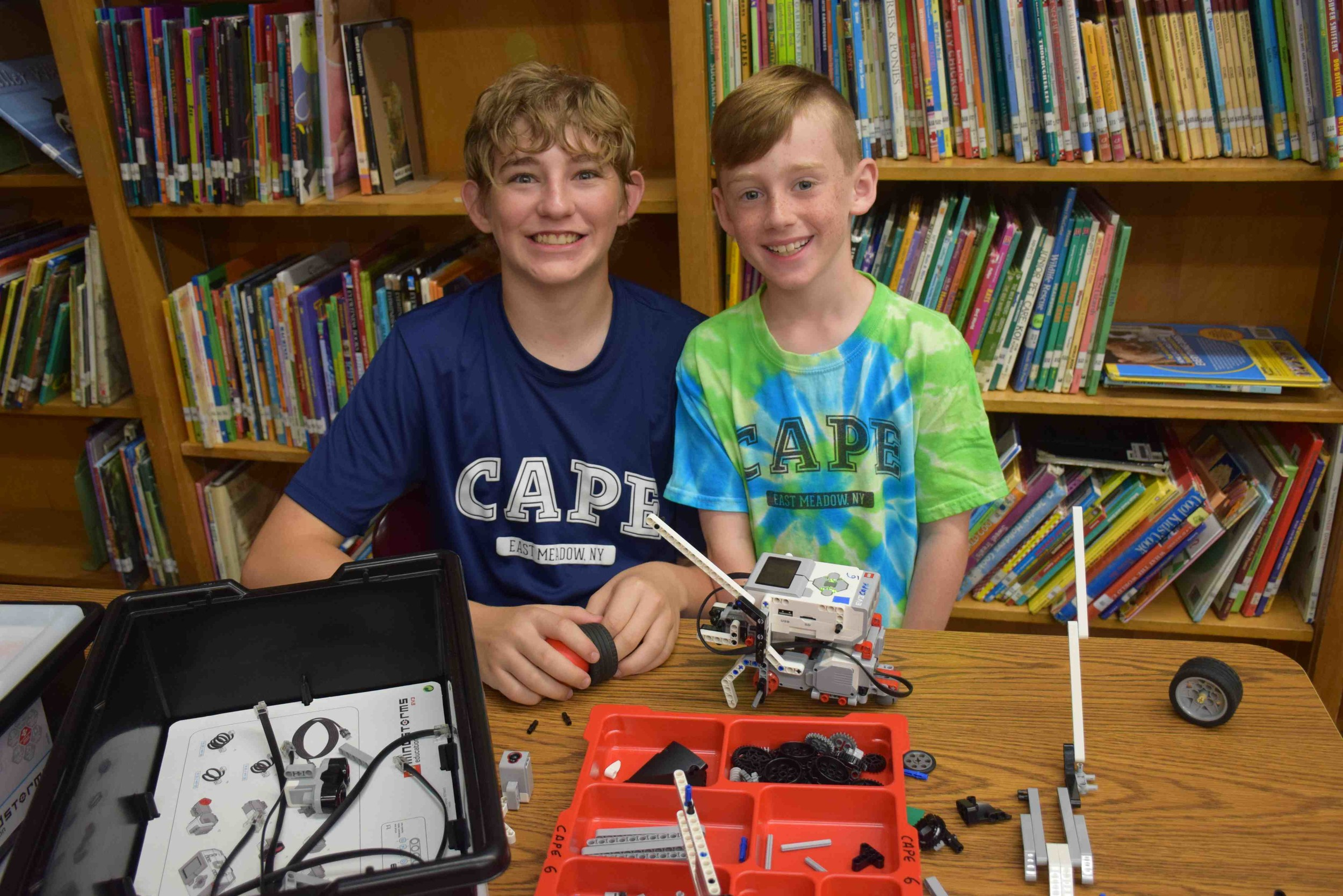 Maverick Kandel (left), a counselor with the Creative Arts Program of East Meadow and sophomore at W.T. Clarke High School, helped McVey Elementary School fourth-grader Thomas Primrose assemble a robot during a robotics class.