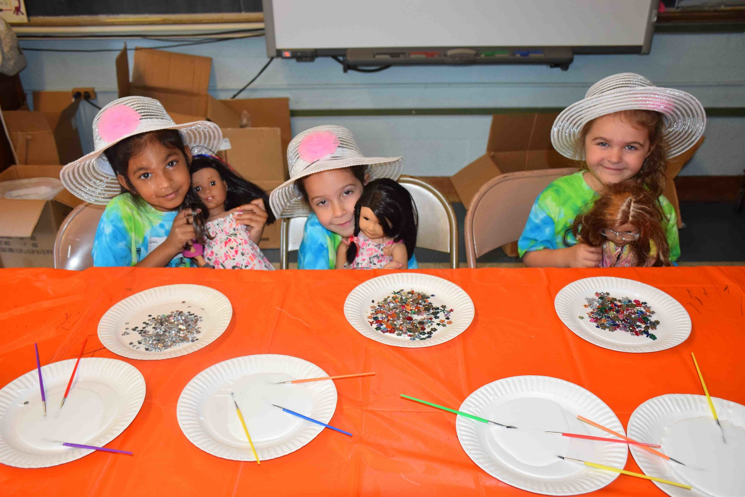 Young students in the Creative Arts Program of East Meadow decorated dolls' hats during their American Girl Party class.