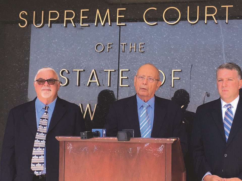 Attorney Steve Cohn, left, former U.S. Sen. Alfonse D'Amato and attorney Christian Browne announced that they were filing a lawsuit against the city's Zoning Board of Appeals, its building commissioner and a subsidiary of the developer iStar outside the Nassau County Supreme Court building on Aug. 3.