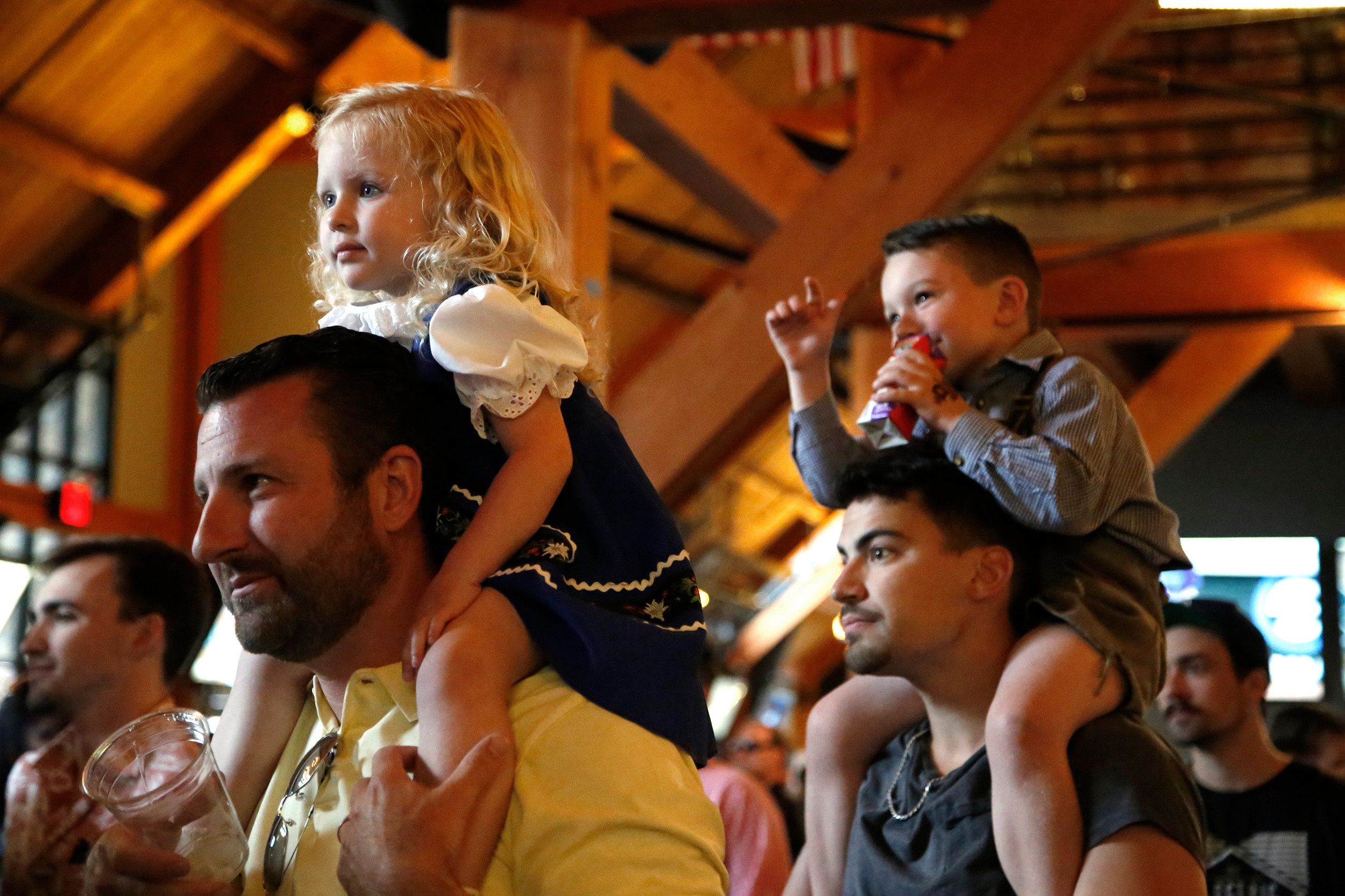 Cameron Wilkins (2) and Ashton Wilkins (4) have a bird's eye view of their mom while sittle on dad and cousin's shoulders, Christopher Wilkins and Steven Liguori.