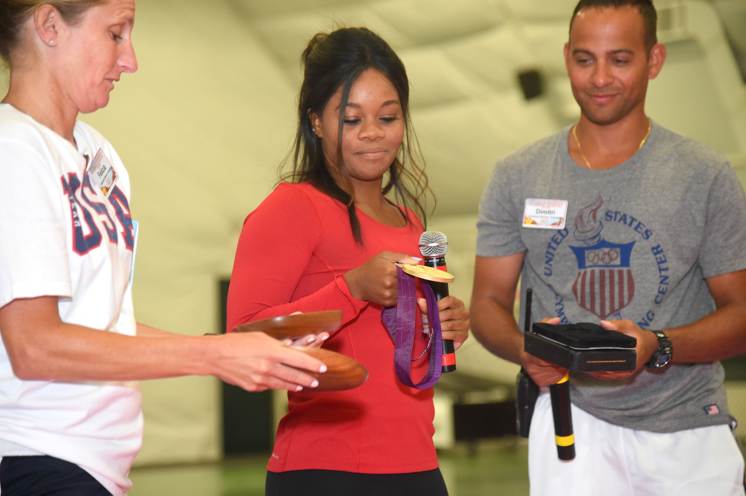 Douglas, joined by two camp employees, showed her medals to campers.