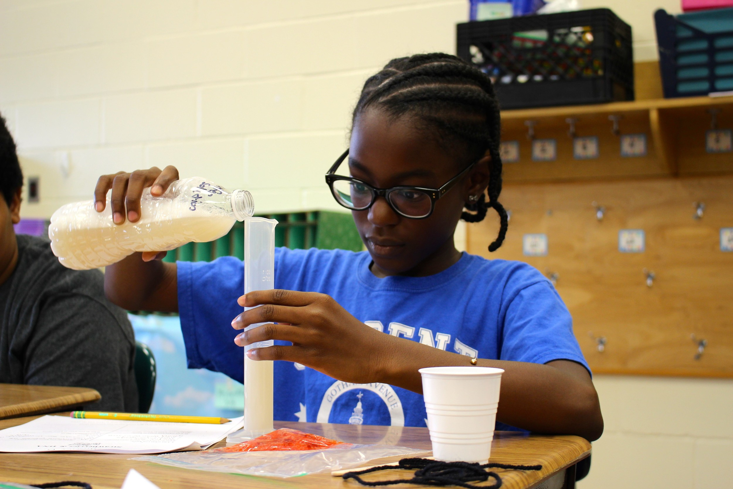 Gotham Avenue School student Aliana Bryan poured a soap and salt mixture into a graduated cylinder to facilitate the extraction.